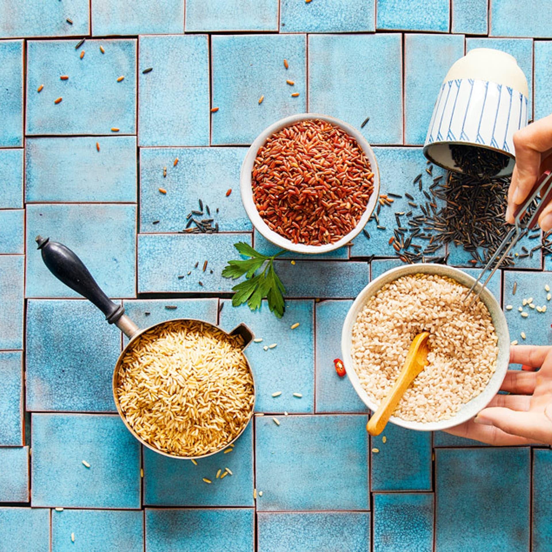 Auf türkisen Fliesen stehen drei Schüsseln mit Reis in verschiedenen Farben: beige, braun und dunkelbraun. Von rechts berührt eine Hand eine der Schüsseln.