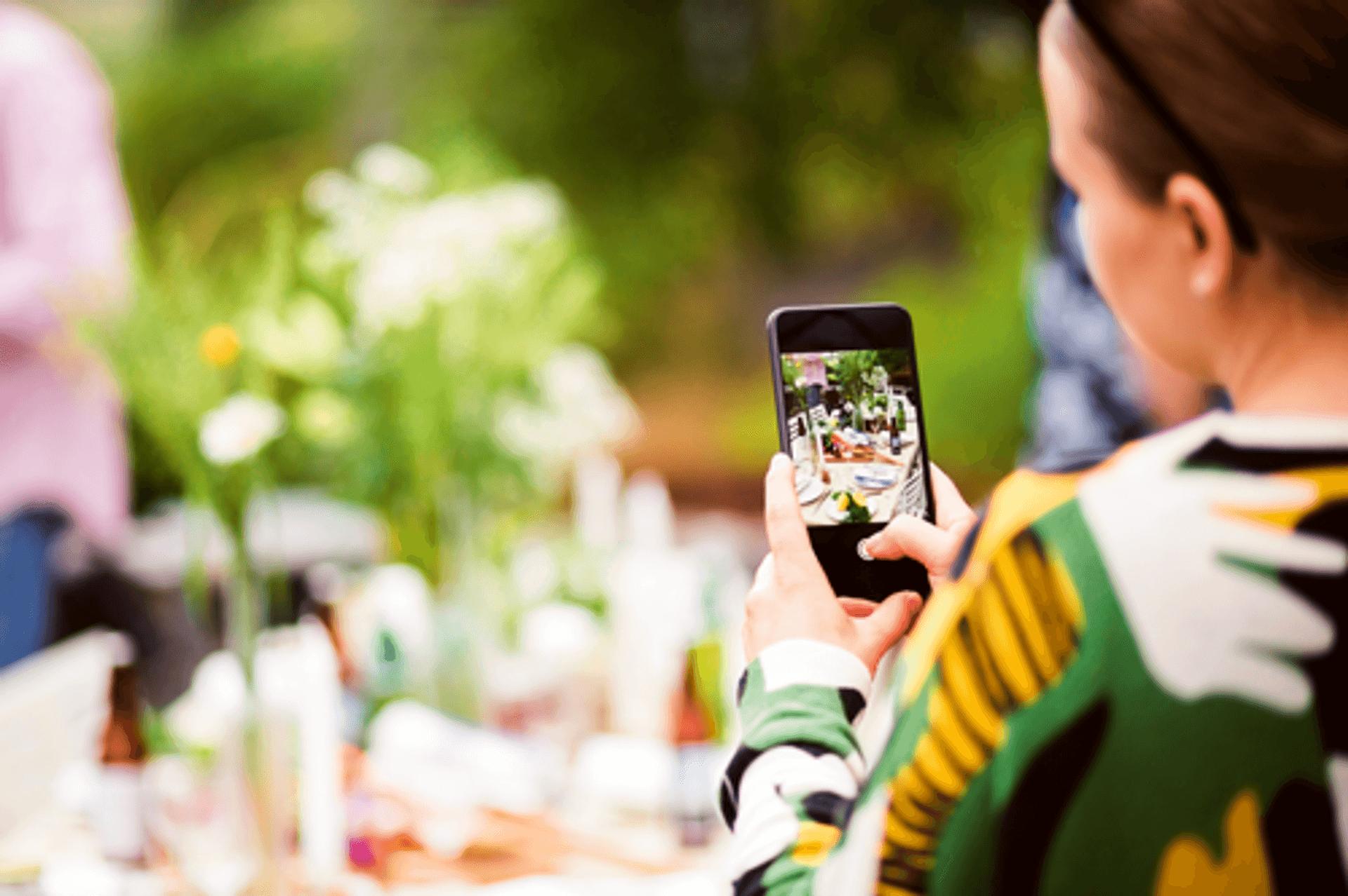 Eine Frau sitzt mit dem Rücken zu uns im Garten und hält ein Handy in der Hand, mit dem sie gerade ein Foto macht. Der Hintergrund ist verschwommen, nur auf dem Bildschirm sieht man scharf den gedeckten Gartentisch, den sie fotografiert.