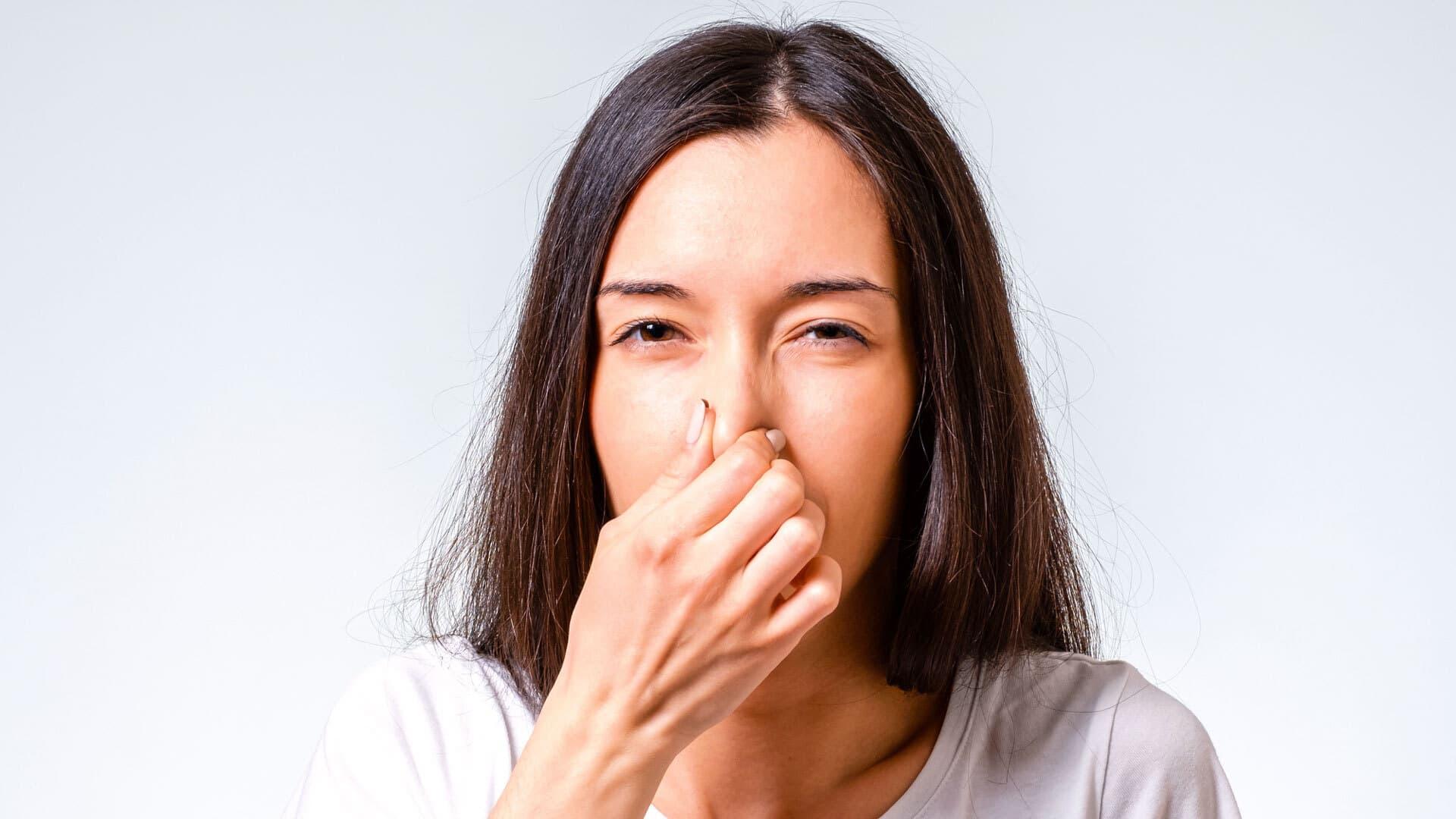 Eine Frau hält sich die Nase zu