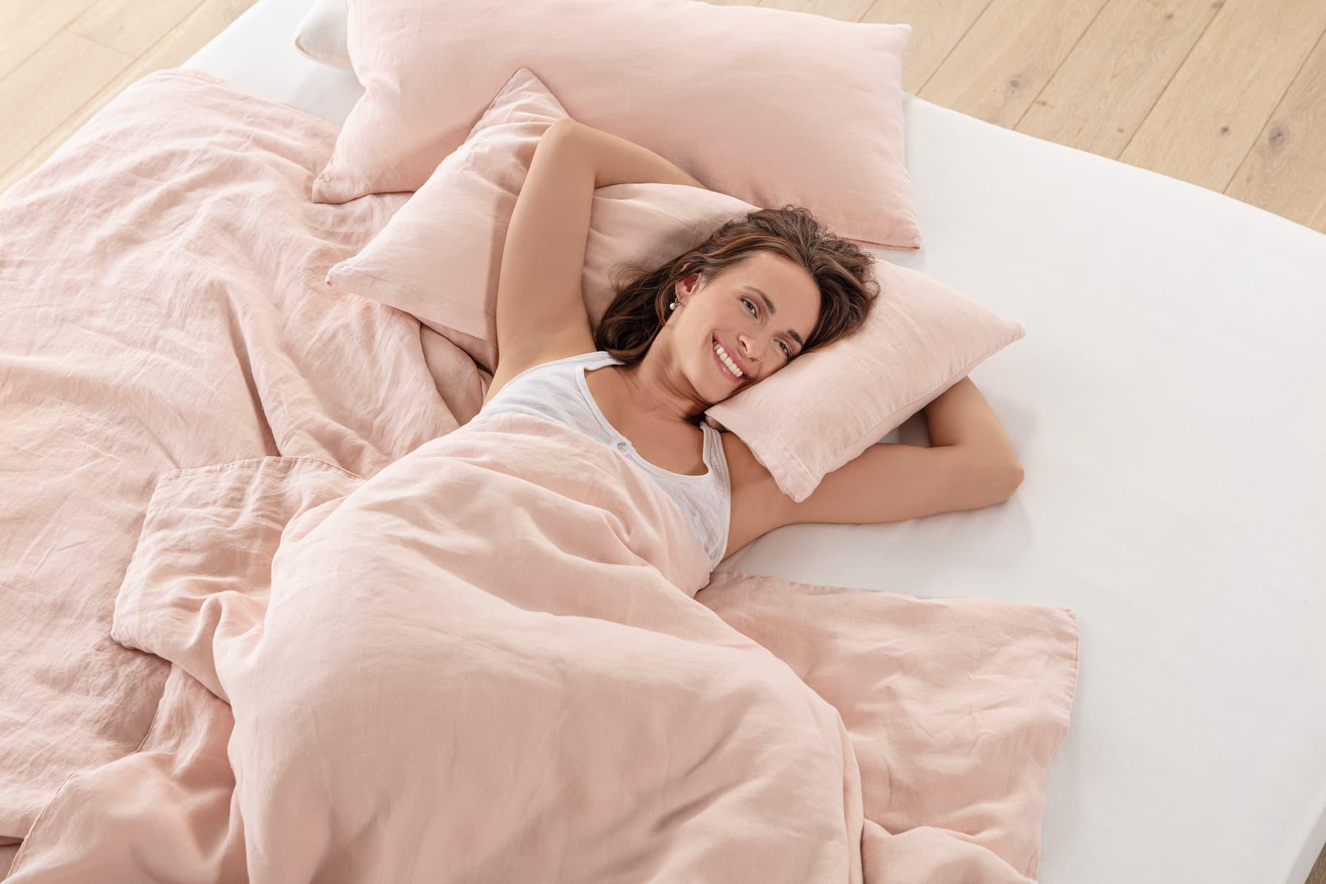 Frau im Bett mit Hanfbettwäsche