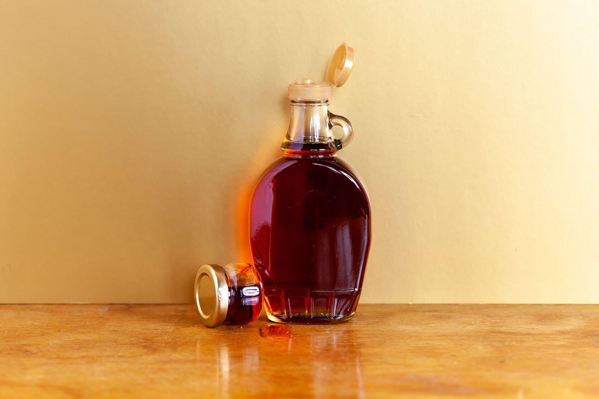 Eine Glasflasche Ahornsirup mit geöffnetem Deckel vor einer hellen Wand