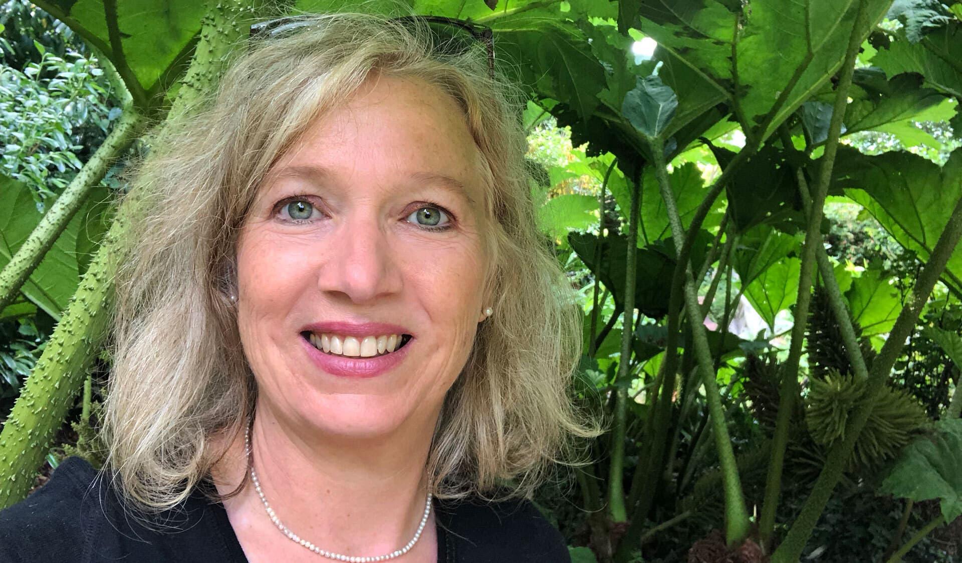 Porträt von Eliane Zimmermann vor einer grünen Pflanzenwand.