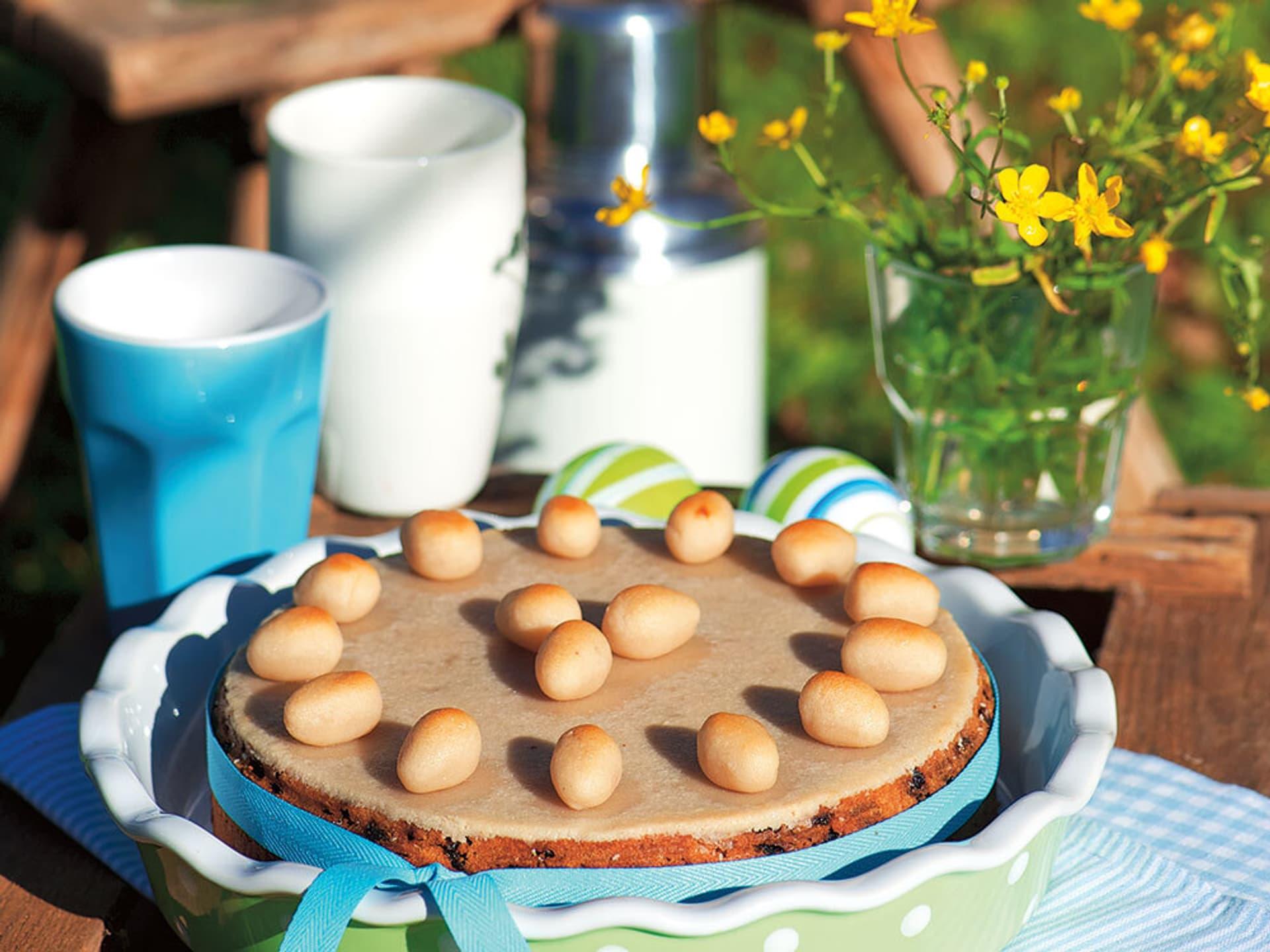 Ein Früchtekuchen verziert mit Ostereiern aus Marzipan und einem hellblauen Band