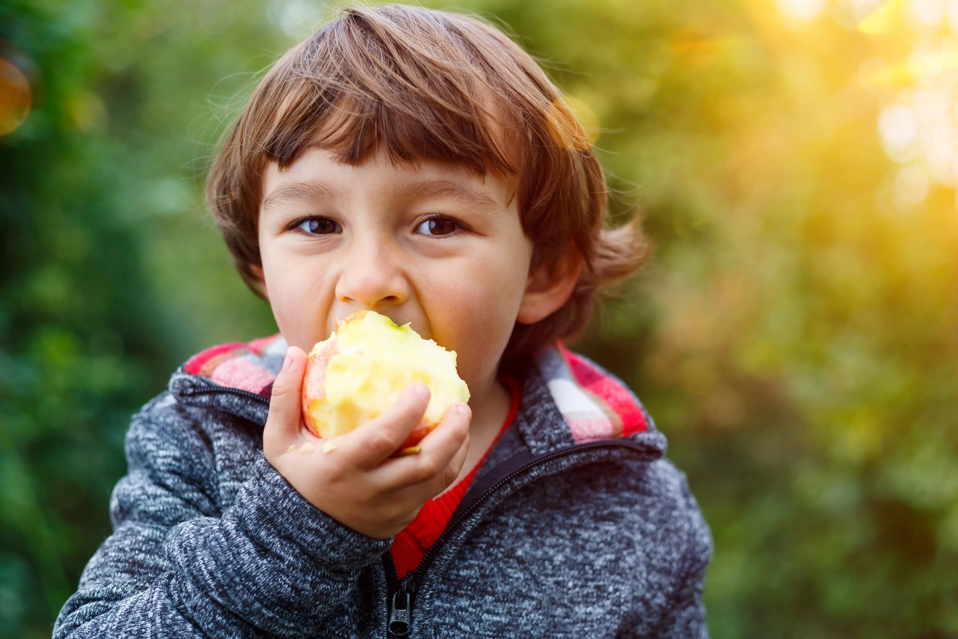 Junge isst Apfel