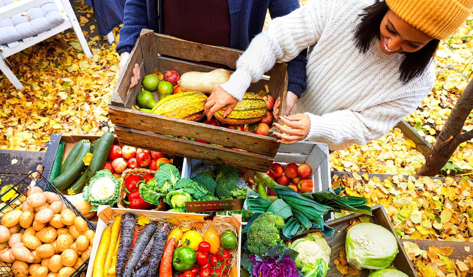 Eine Frau packt Obst und Gemüse in eine Holzkiste