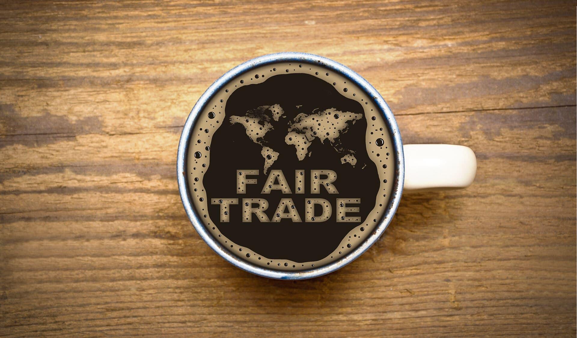 Eine Tasse Kaffee von oben mit Schaum, der die Wörter Fair Trade bildet