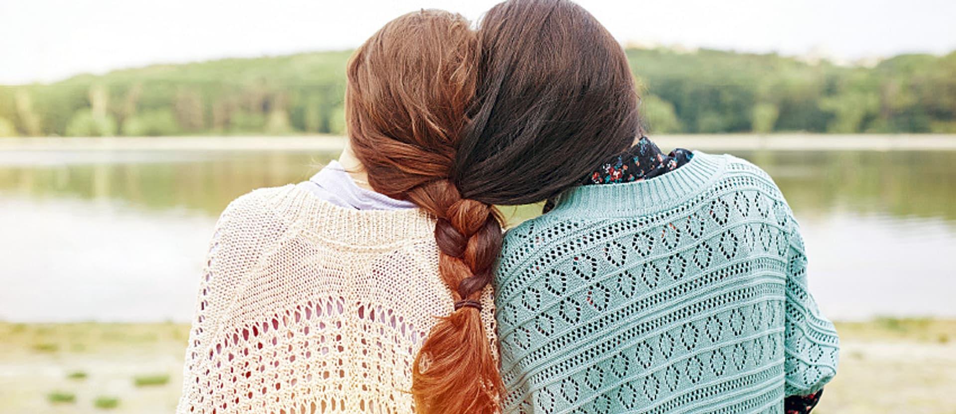 Zwei Schwestern mit zusammengeflochtenem Haar, schauen zu einem See.
