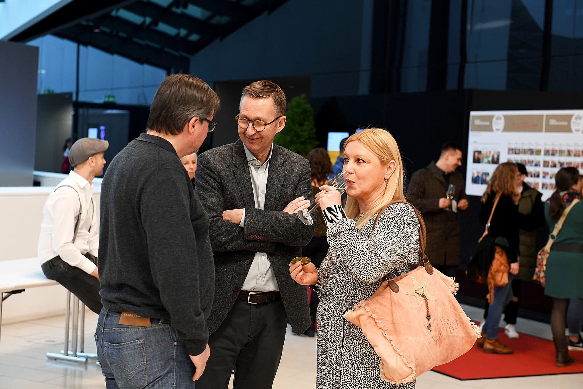 Drei Personen unterhalten sich bei einem Cocktail.