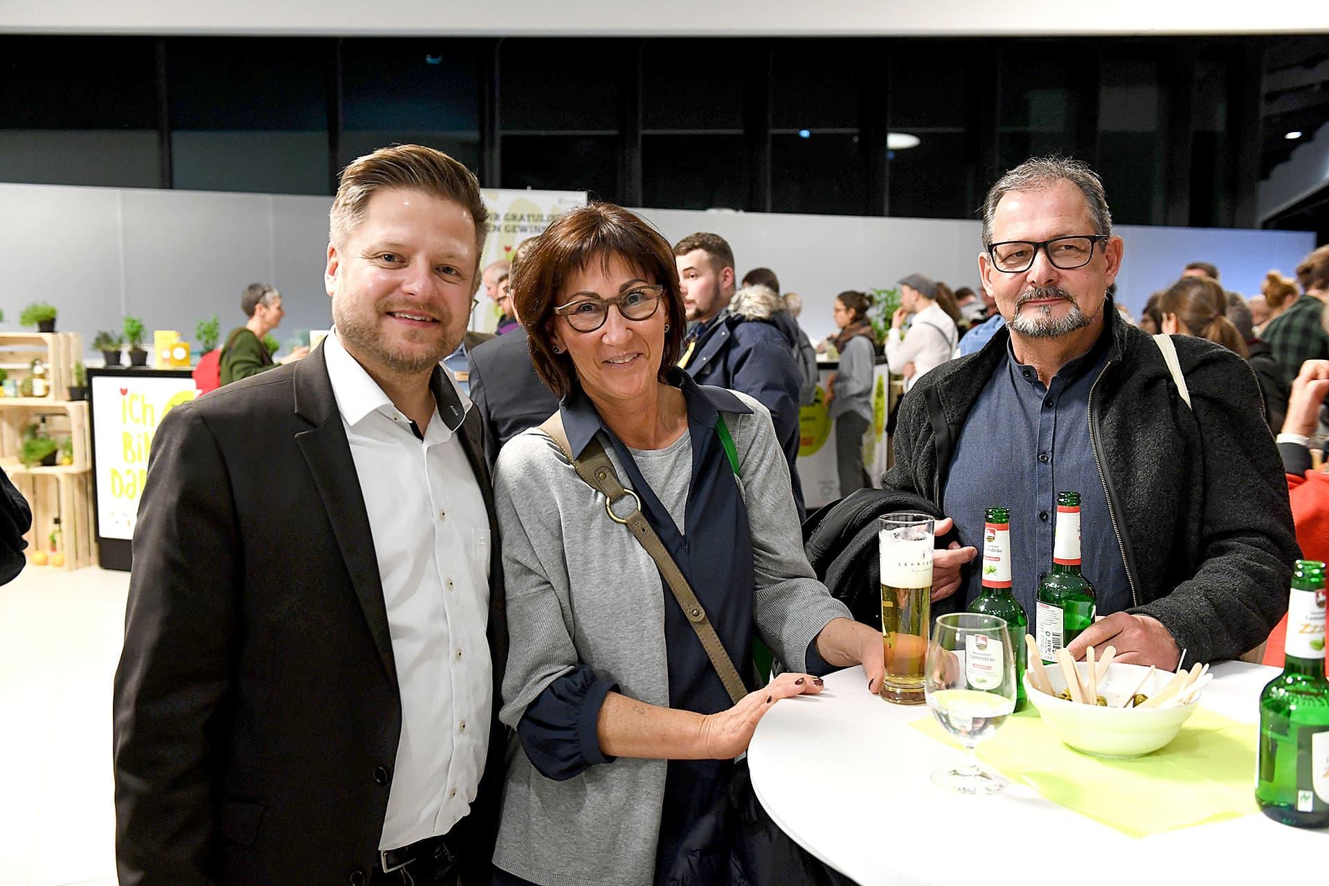 Drei Teilnehmer an der Gala posieren für ein Foto am Stehtisch.