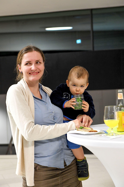 Lächelnde Frau mit Kind auf dem Arm.