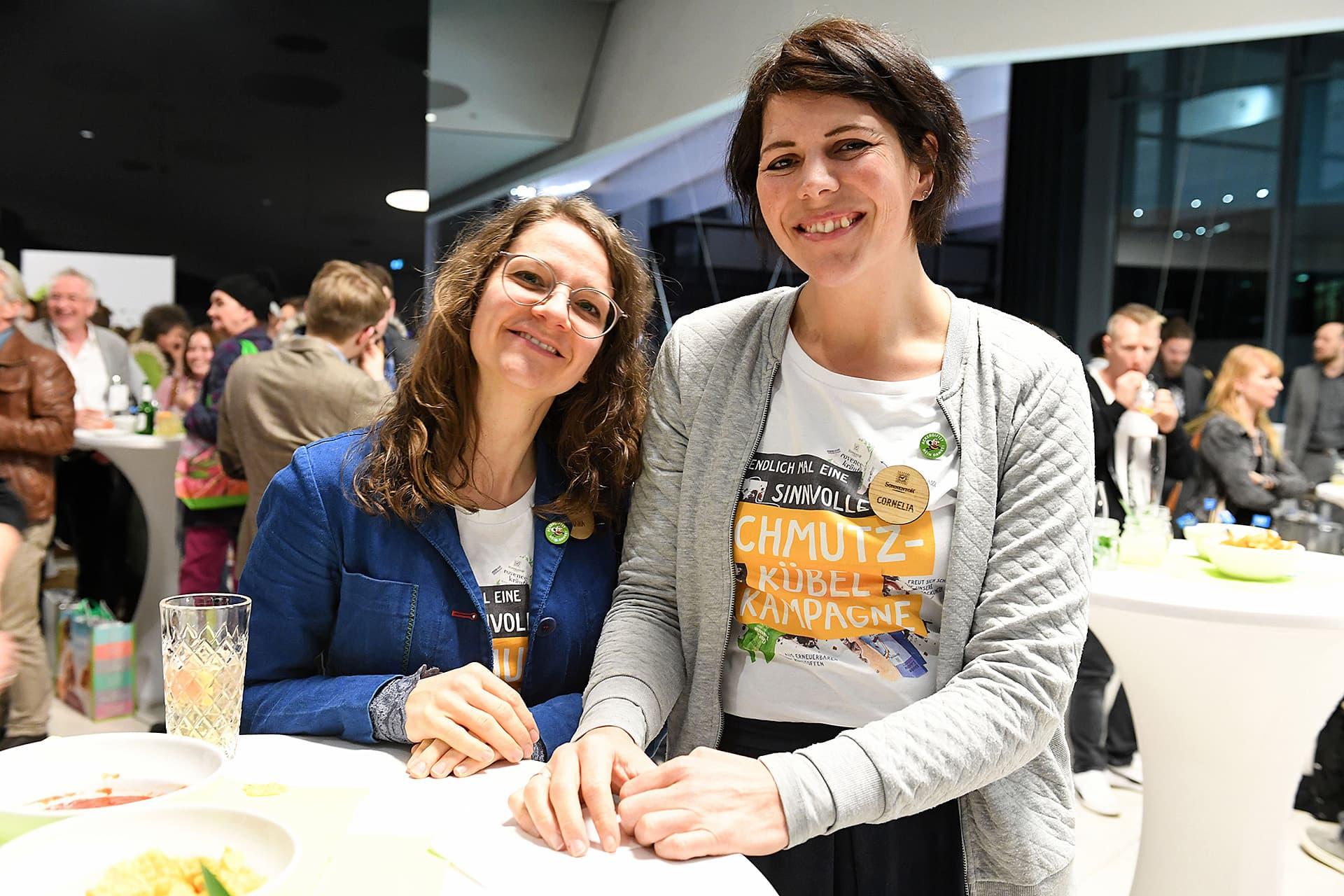 Zwei Mitarbeiterinnen von Sonnentor posieren lächelnd am Stehtisch.