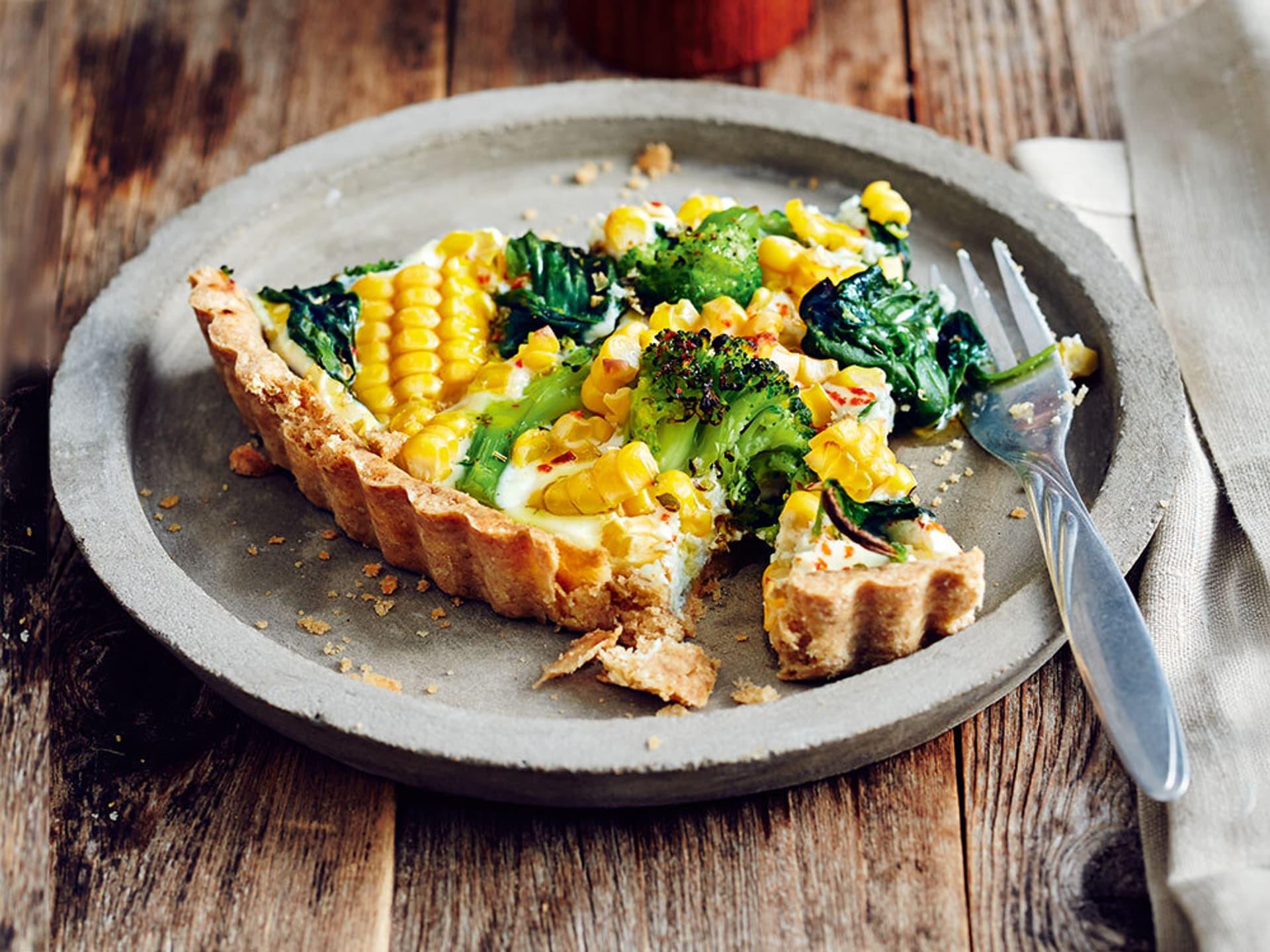 Ein Stück Gemüse-Tarte auf einem grauen Teller
