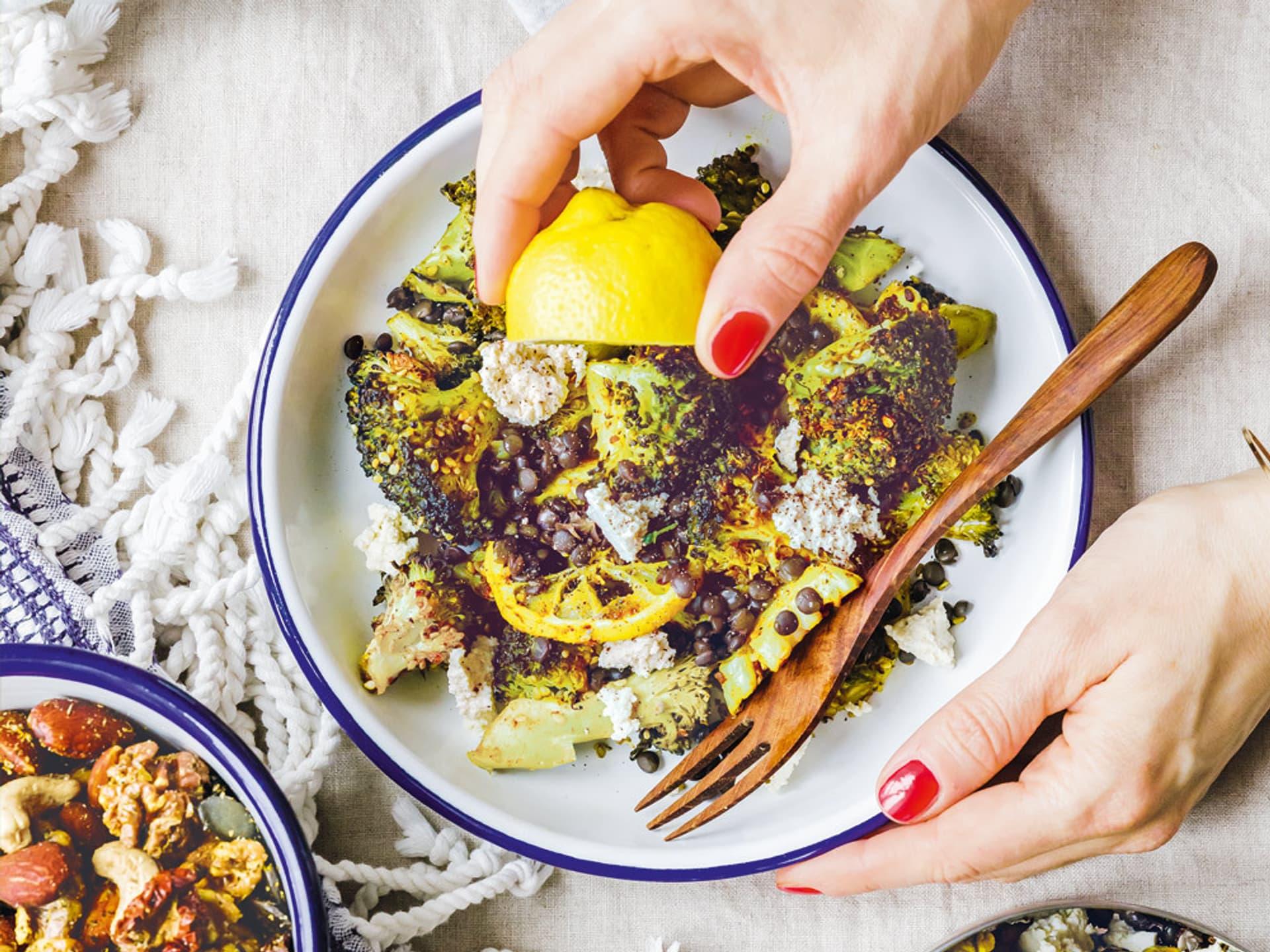 Ein Teller voller Brokkoli wird mit Zitrone beträufelt