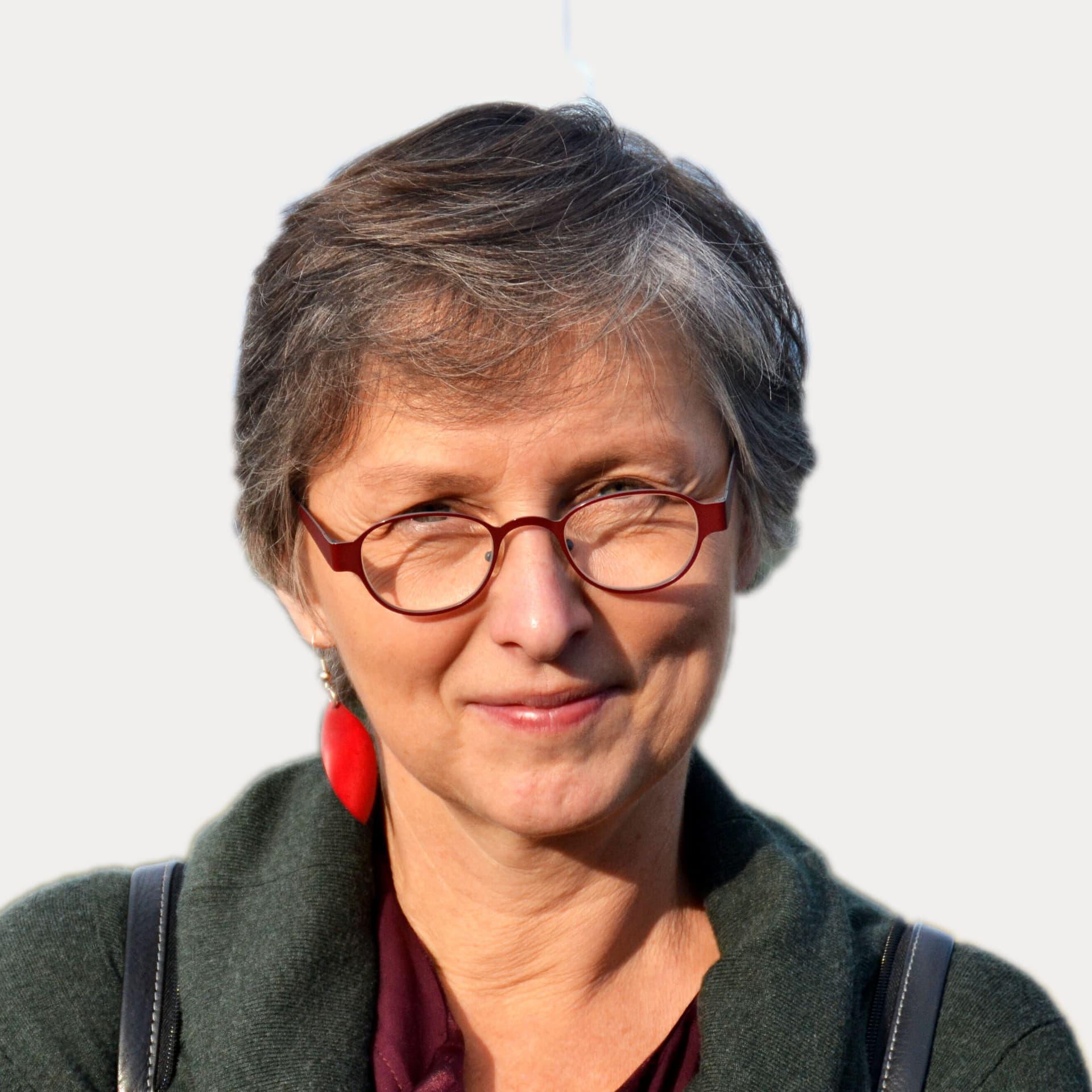 Eine grauhaarige Frau mit dunkelroter Nickelbrille