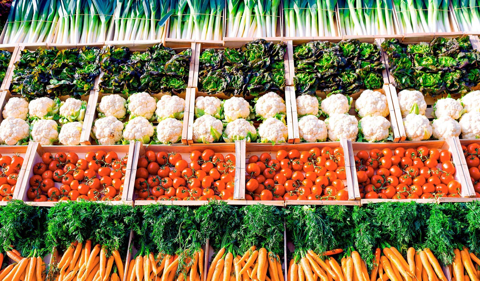 Makellose Tomaten, Blumenkohlköpfe und Möhren im Gemüseregal