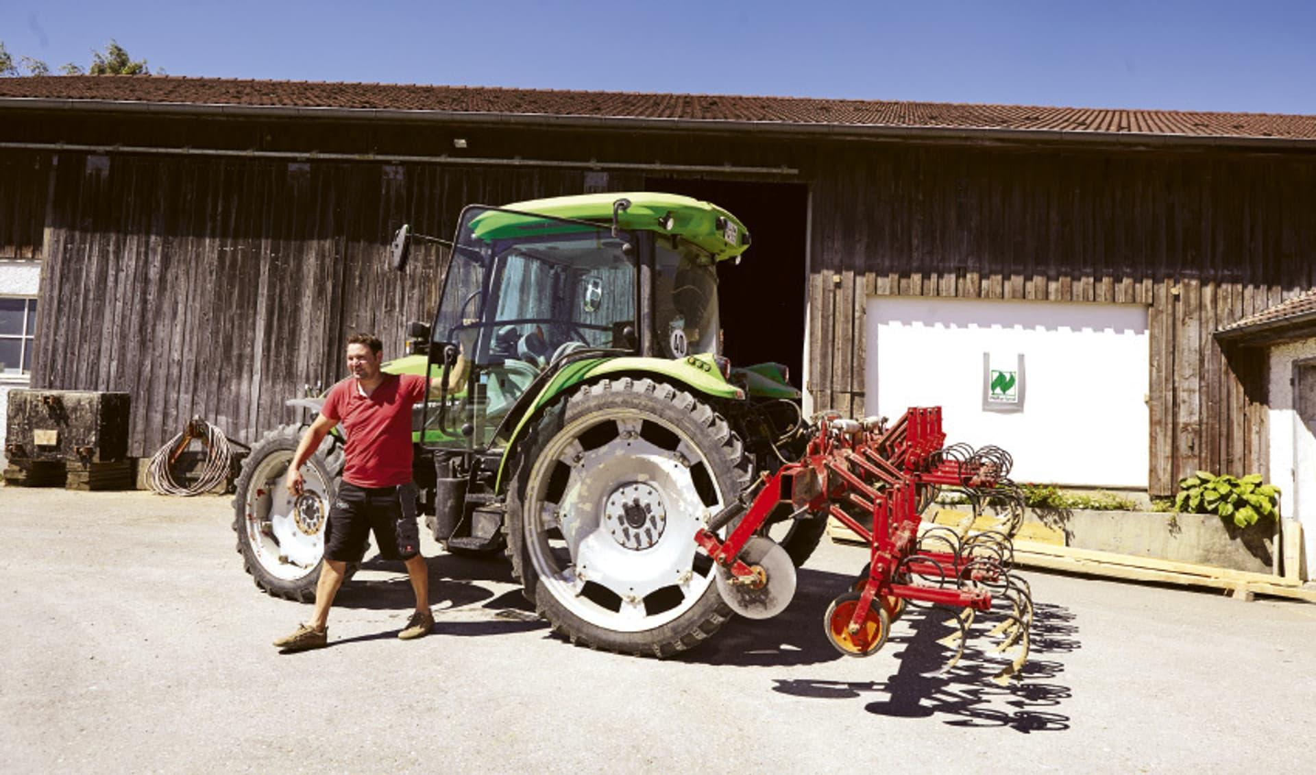 Bauer mit rotem T-Shirt vor seinem Traktor