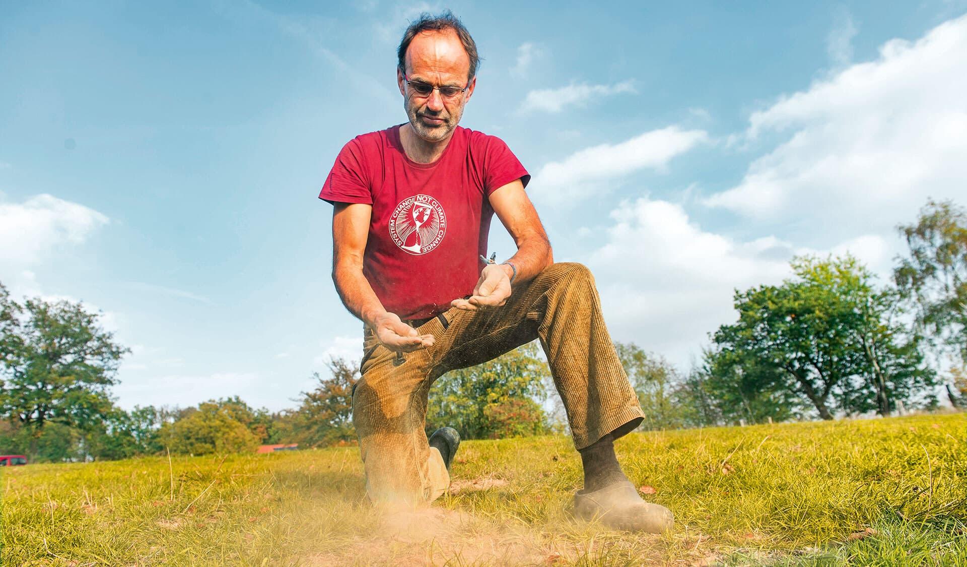 Bio-Bauer Ulf Allhoff-Cramer kniet auf seiner Weide und prüft den Zustand des Bodens.