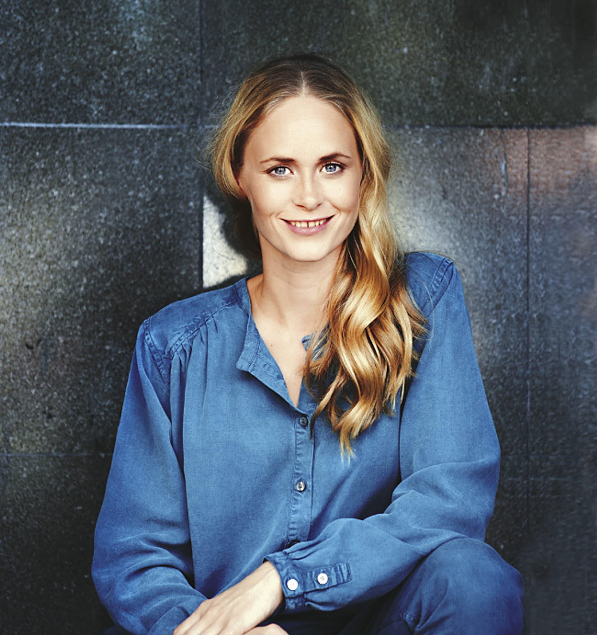 Die Schauspielerin Inez Bjørg David trägt ein blaues Jeanshemd und hat langen, blonden Haare, sie lächelt in die Kamera