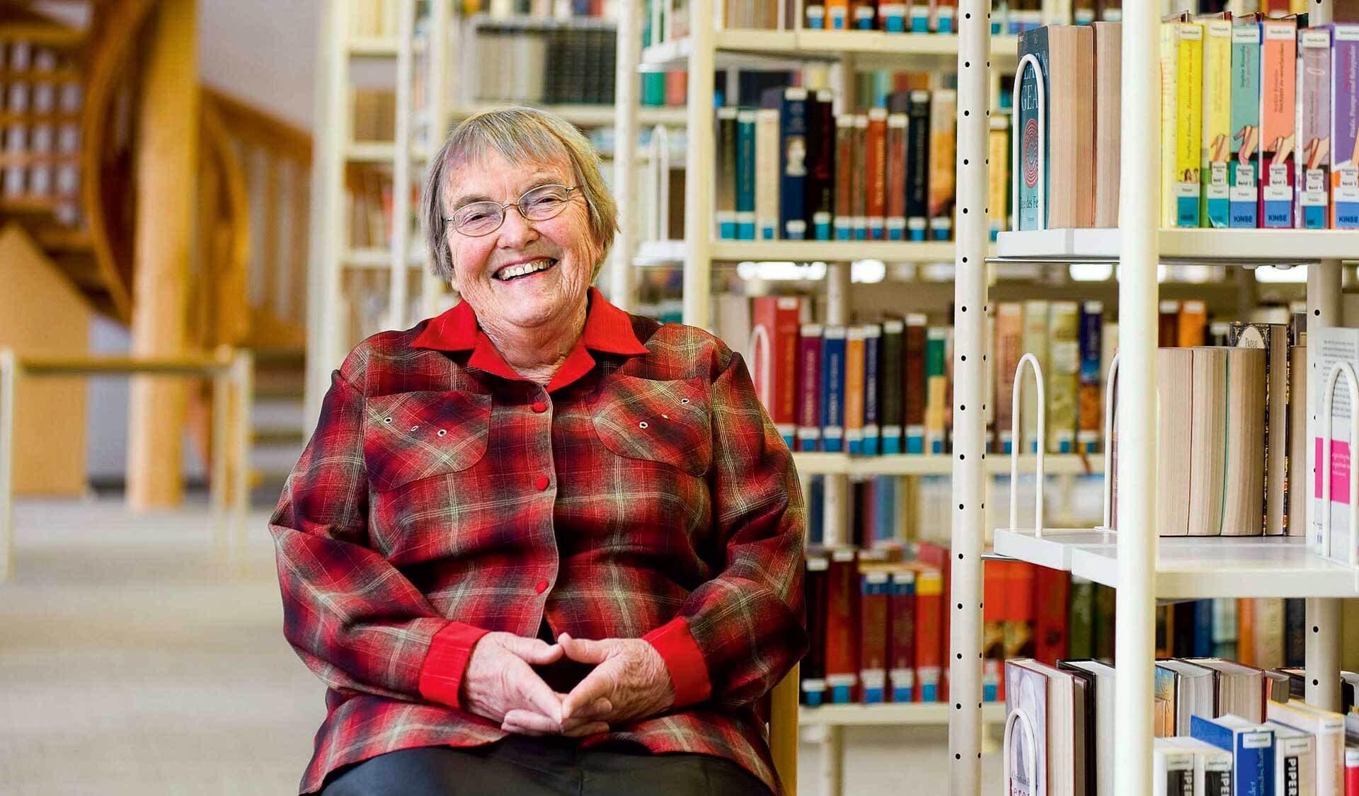 Gudrun Pausewang auf einem Stuhl sitzend - umgeben von Büchern