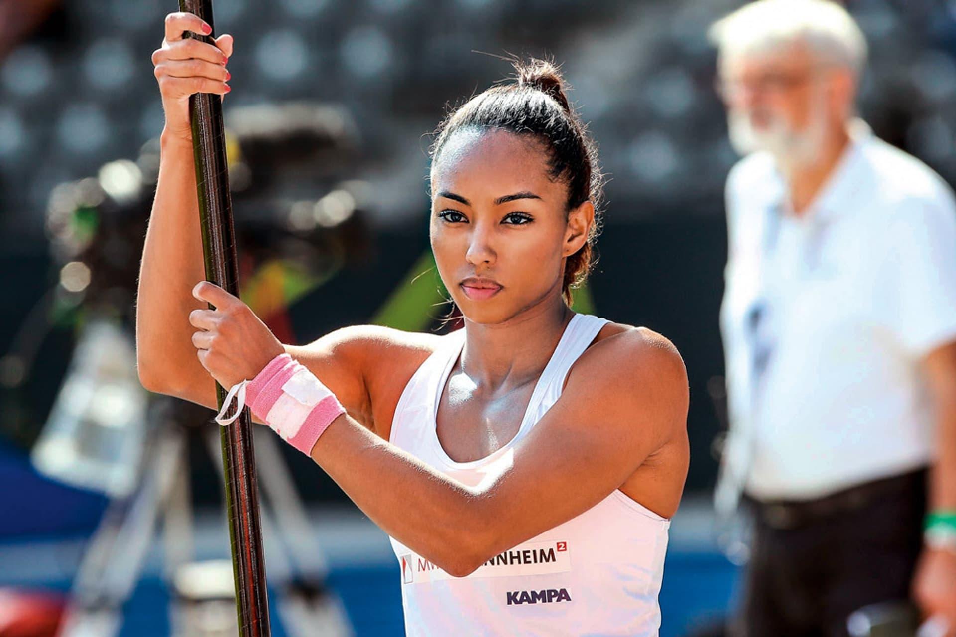 Eine schwarze Frau in Sportkleidung und mit strengem Zopf hält einen Stab in der Hand