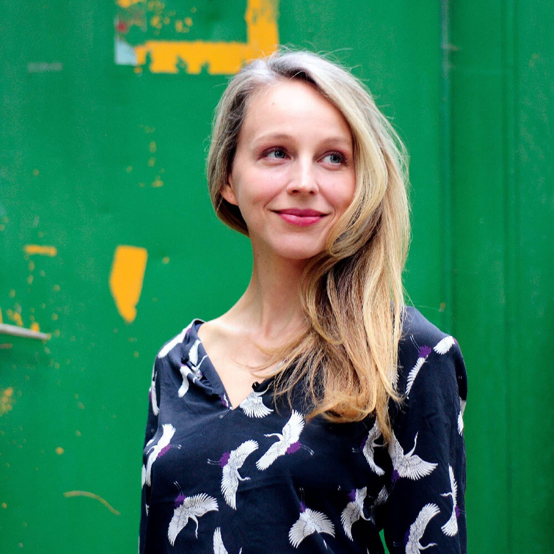 Petra Schmidt-Schaller in einem blauen Kleid mit weißen Vögeln