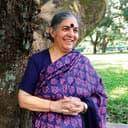 Vandana Shiva lehnt an einem Baum und lächelt