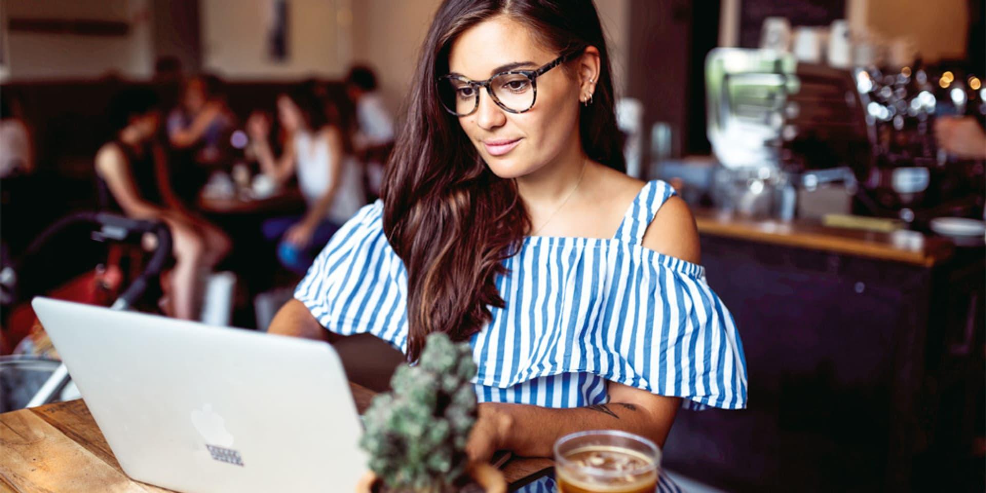 Eine Frau mit langem braunen Haar und dunkler Brille sitzt an ihrem Laptop in einem Café