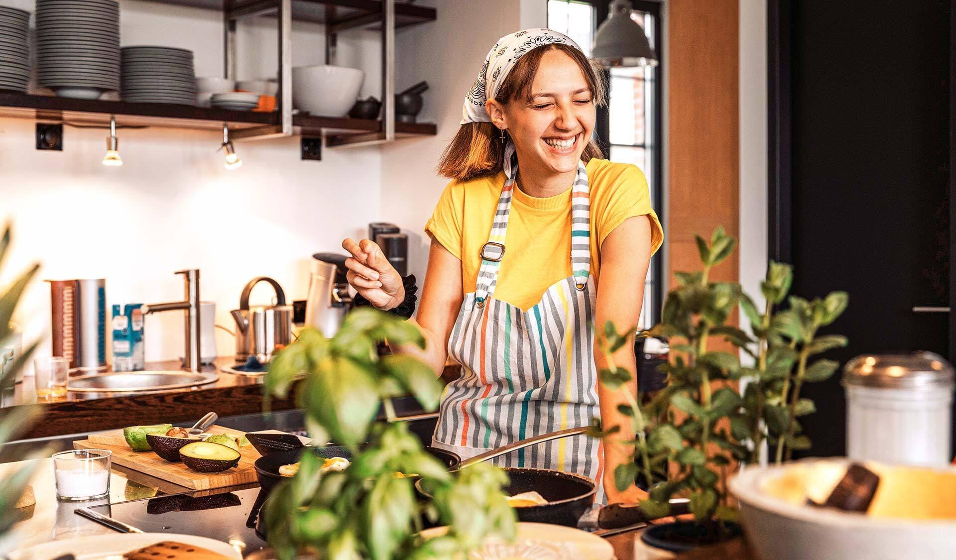 Eine Frau steht lachend in der Küche