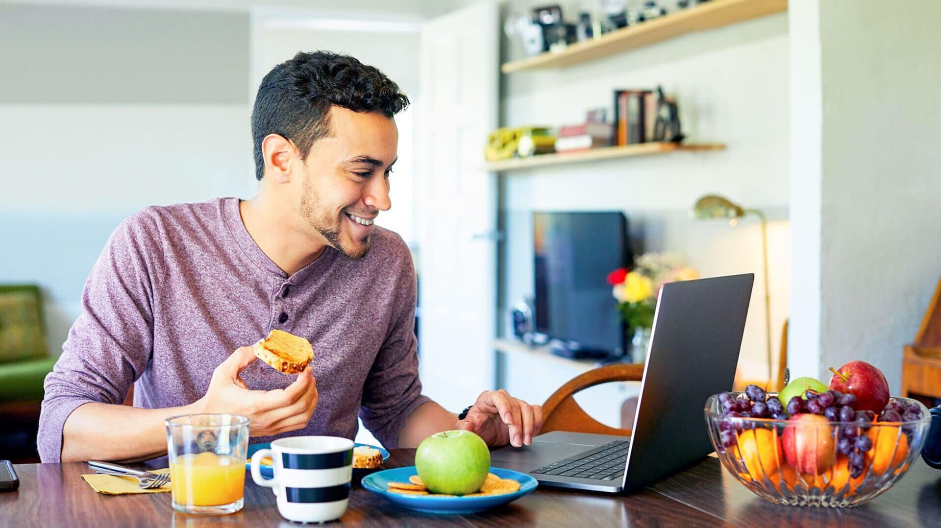Mann mit Brotscheibe in der Hand sitzt an Computer und lacht
