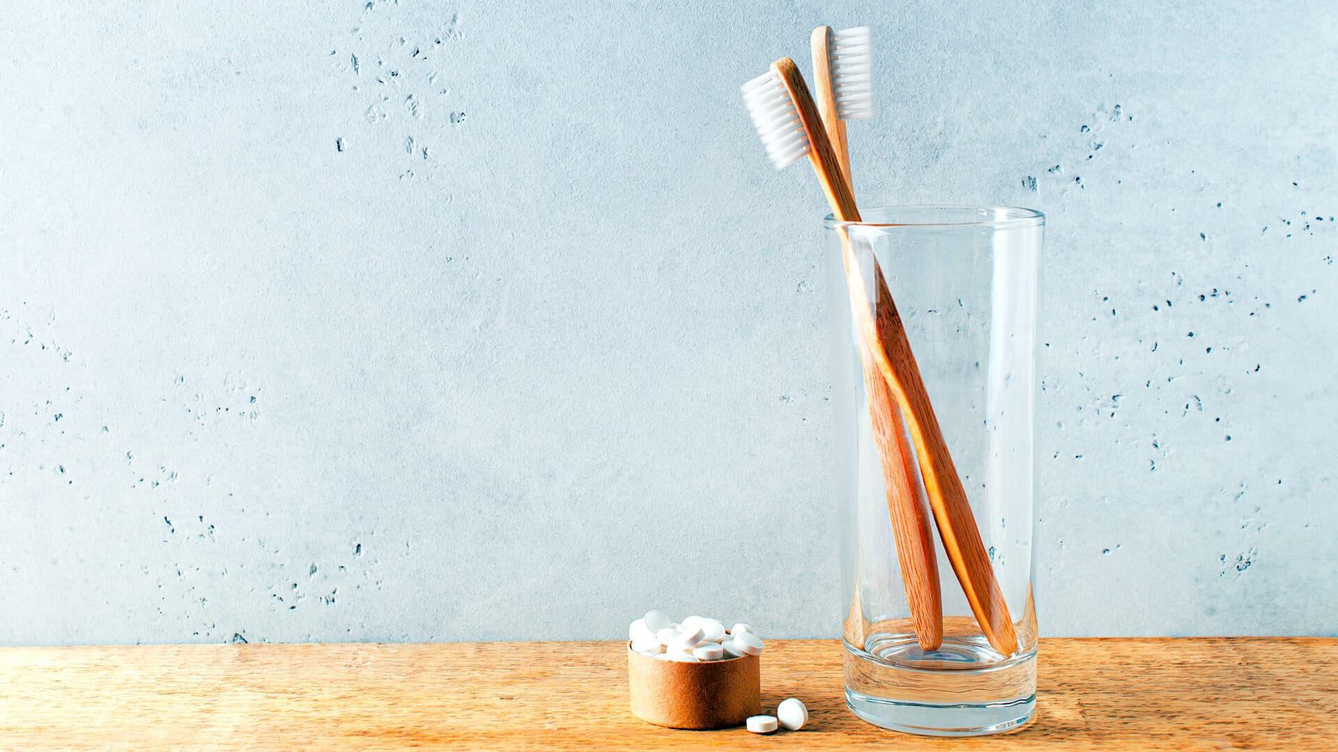 Zwei Bambuszahnbürsten in einem Glas, daneben Zahnputztabletten in einem Döschen.