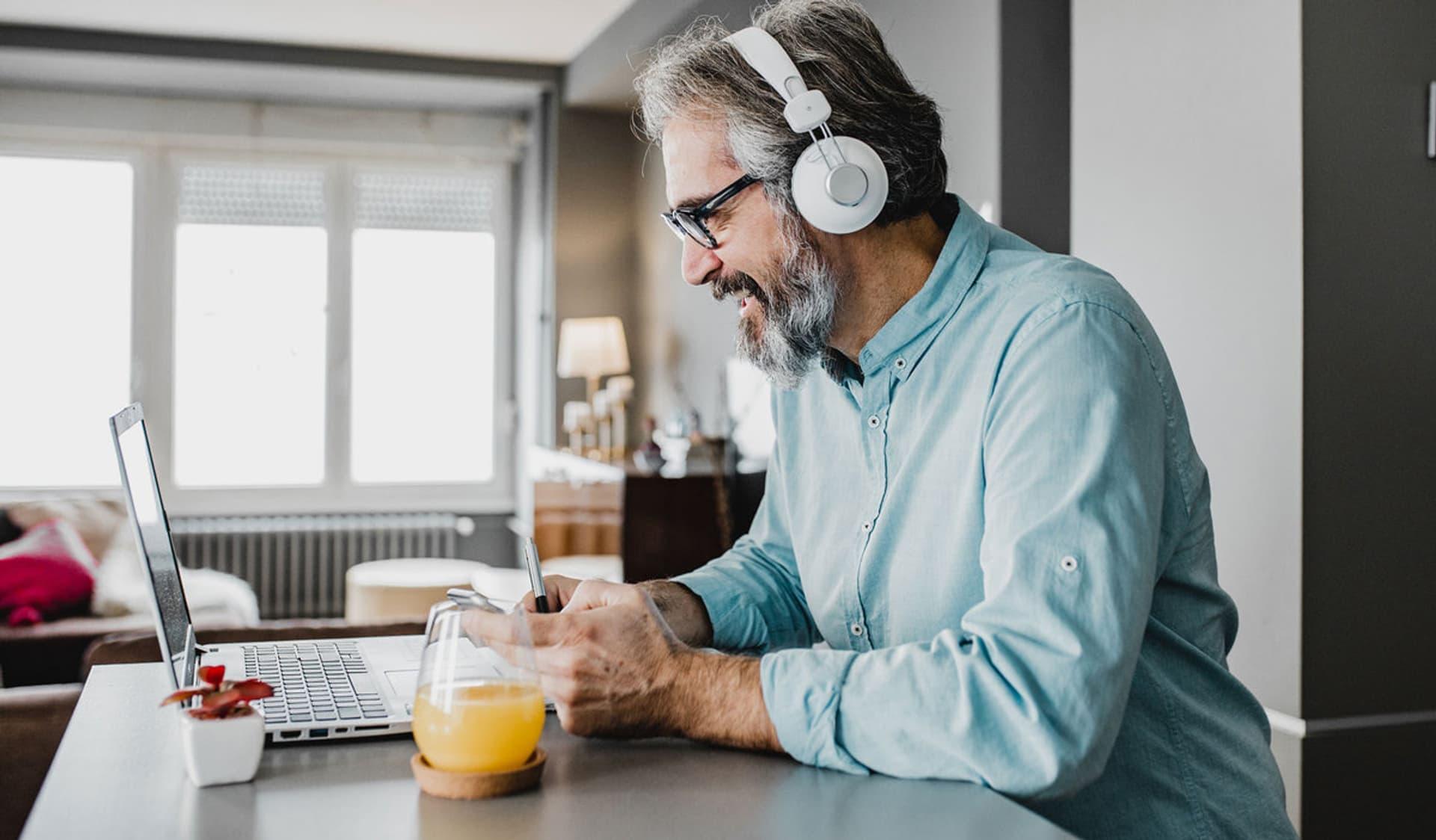 Ein lächelnder Mann mit Kopfhörern sitzt mit einem Glas Orangensaft am Computer.