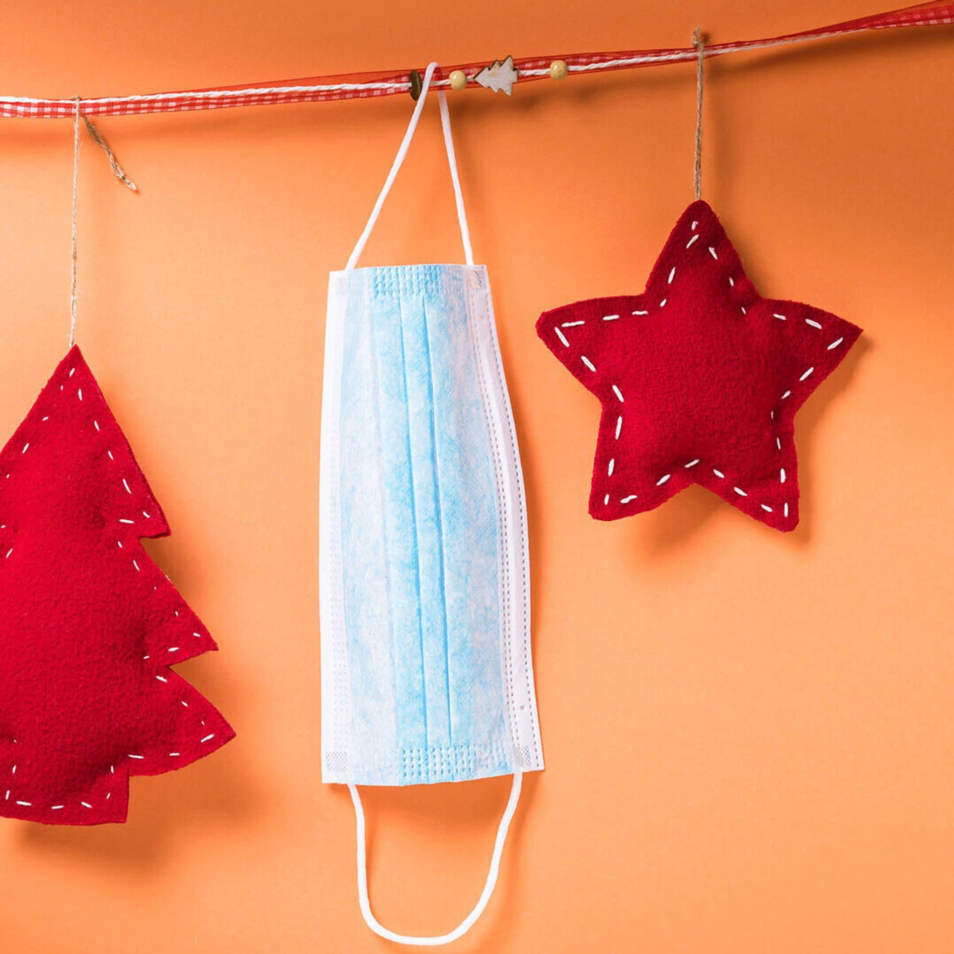 Weihnachtsdekoration und Atemmaske an einer Kette