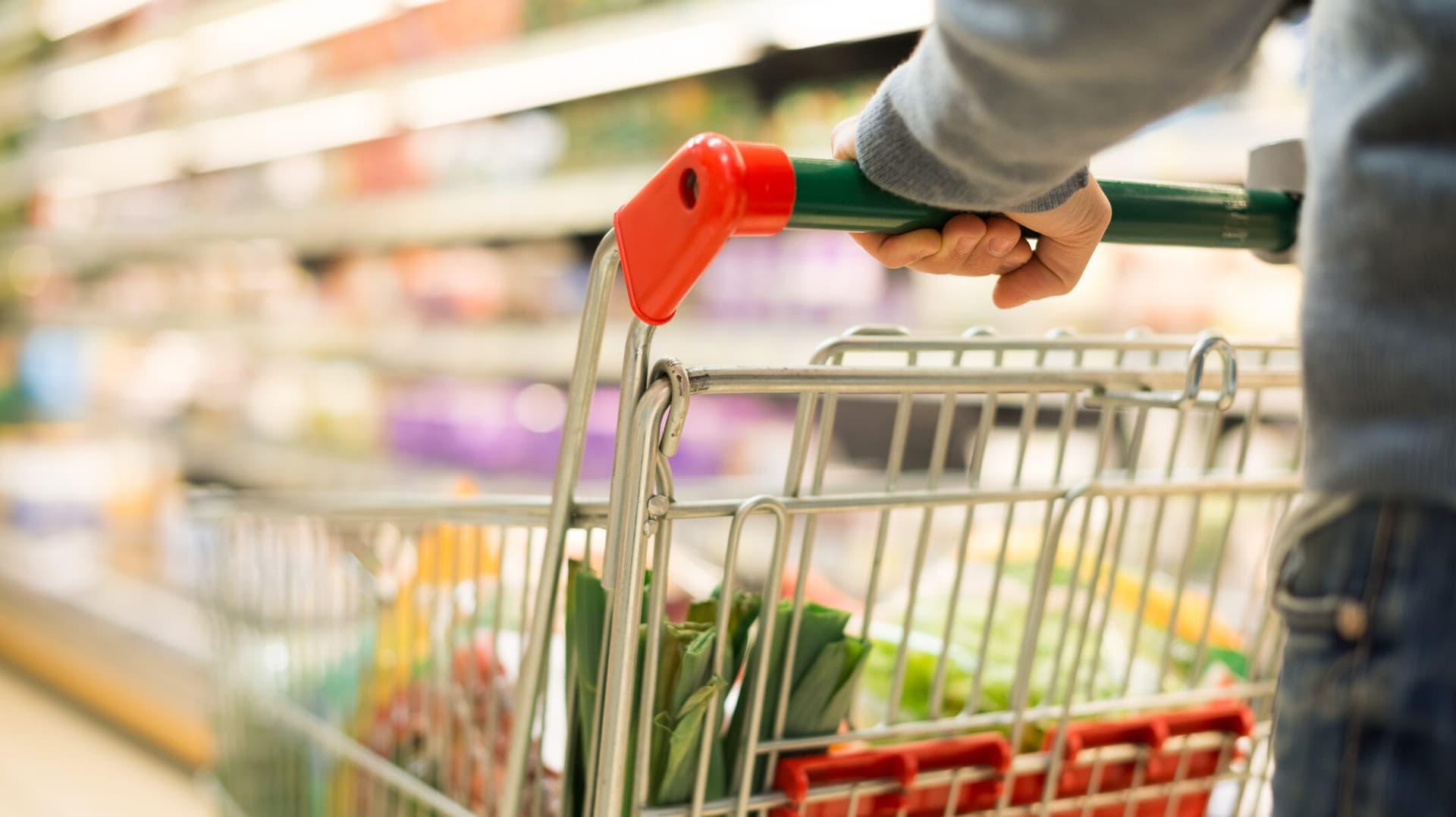 Eine Person schiebt einen Einkaufswagen durch Supermarktregale.