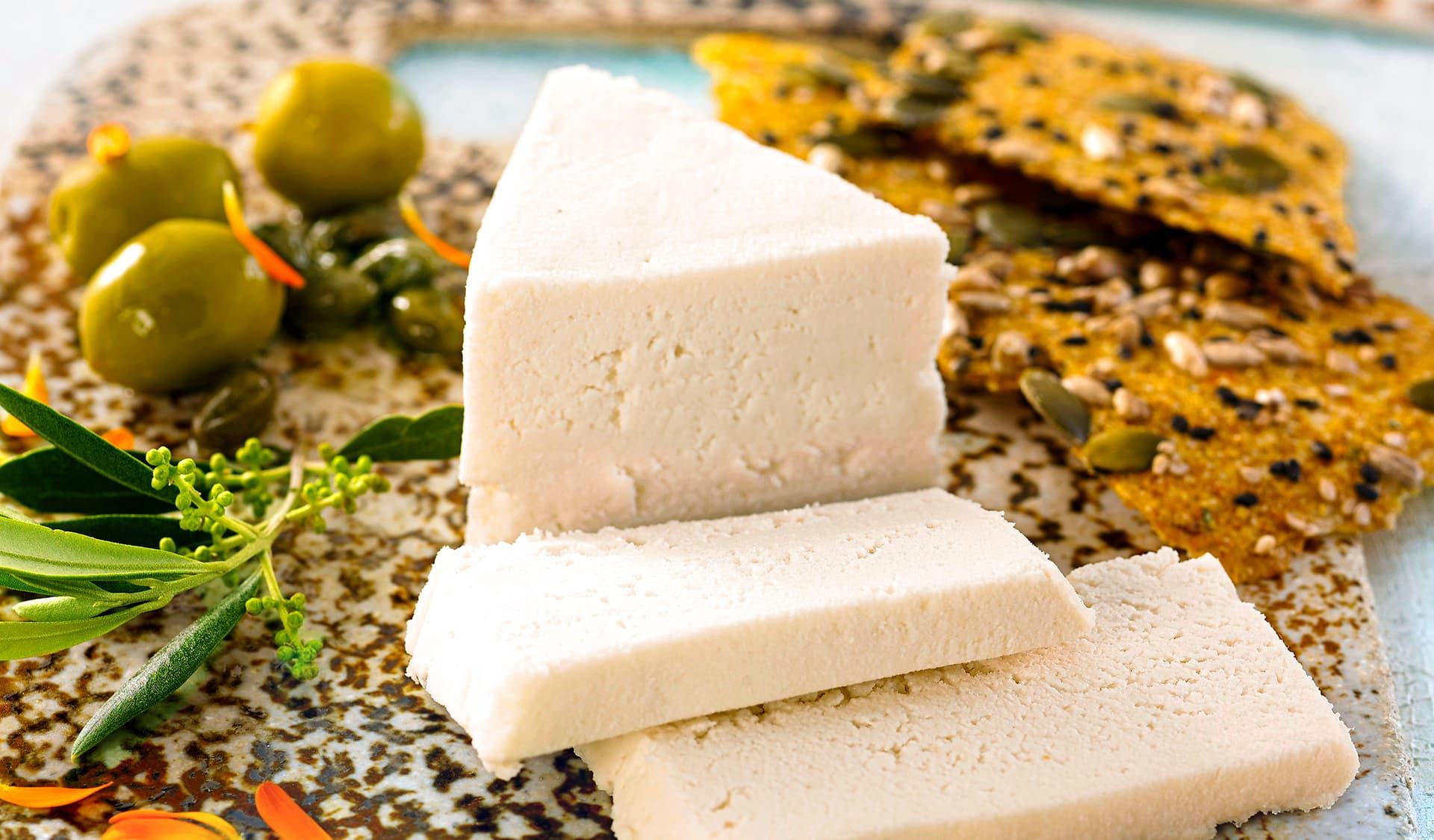weißer veganer Käse mit Knäckebrot und Oliven