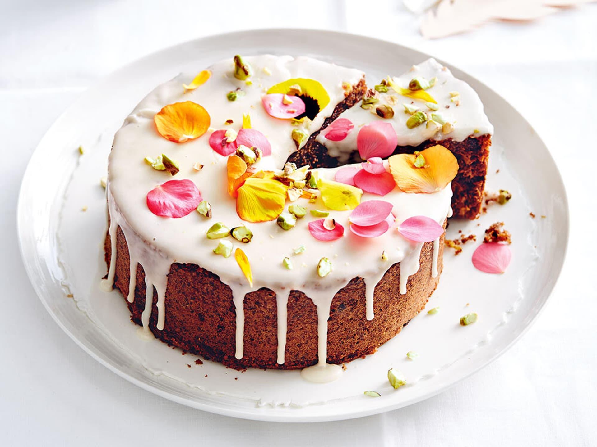 Ein runder Kuchen mit weißem Zuckerguss und bunten Blüten und gehackten Pistazien dekoriert – ein Stück ist angeschnitten
