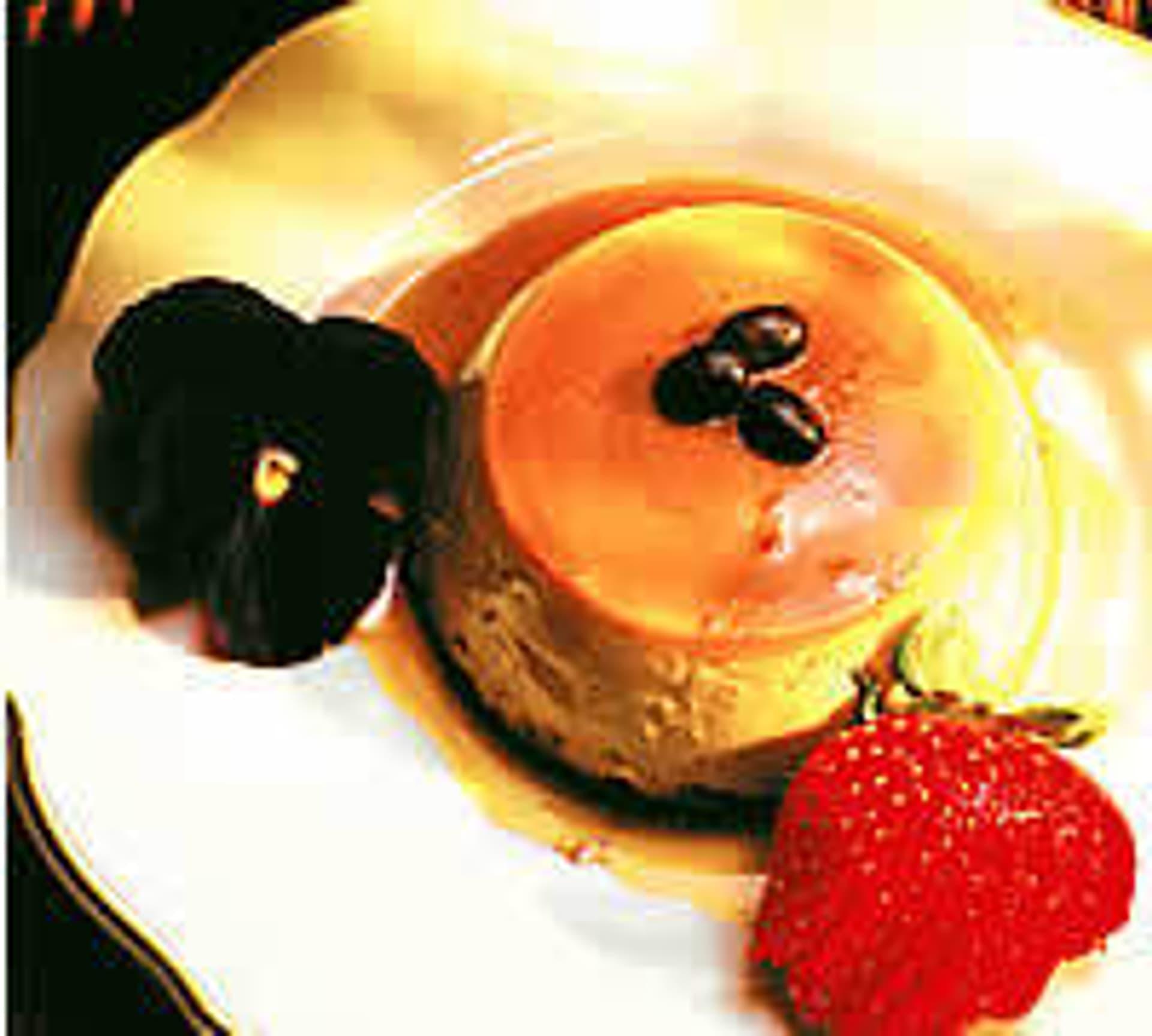 Panna-cotte auf einem weißen Teller, dekoriert mit einer Blüte und einer Erdbeere.