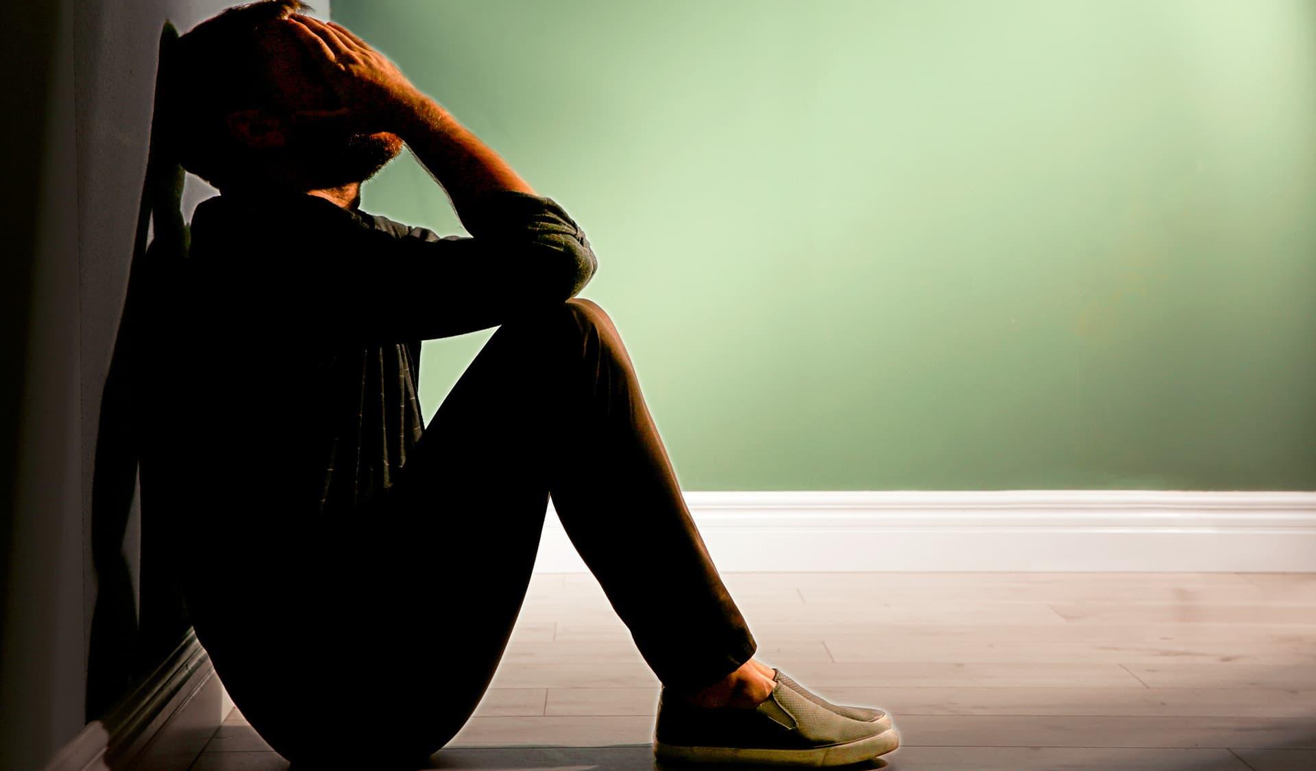 Ein Mann sitzt am Boden, die Beine angezogen und hält die Hände vor sein Gesicht.