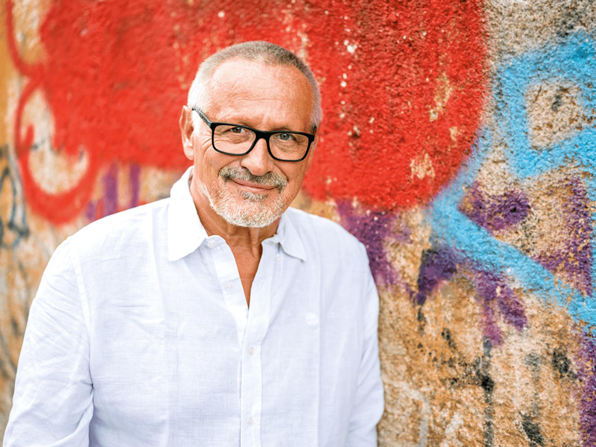 Ein Mann in weißem Hemd mit hellgrauen Haar und kurzem Vollbart und einer markanten schwaren Brille. er stet vor einer Graffiti-Wand und lächelt.