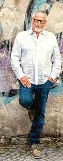 Konstantin Wecker steht in Blue Jeans und weißem Hemd an eine bunte Wand angelehnt. Sein Haar ist weiß, die Brille groß und schwarz.