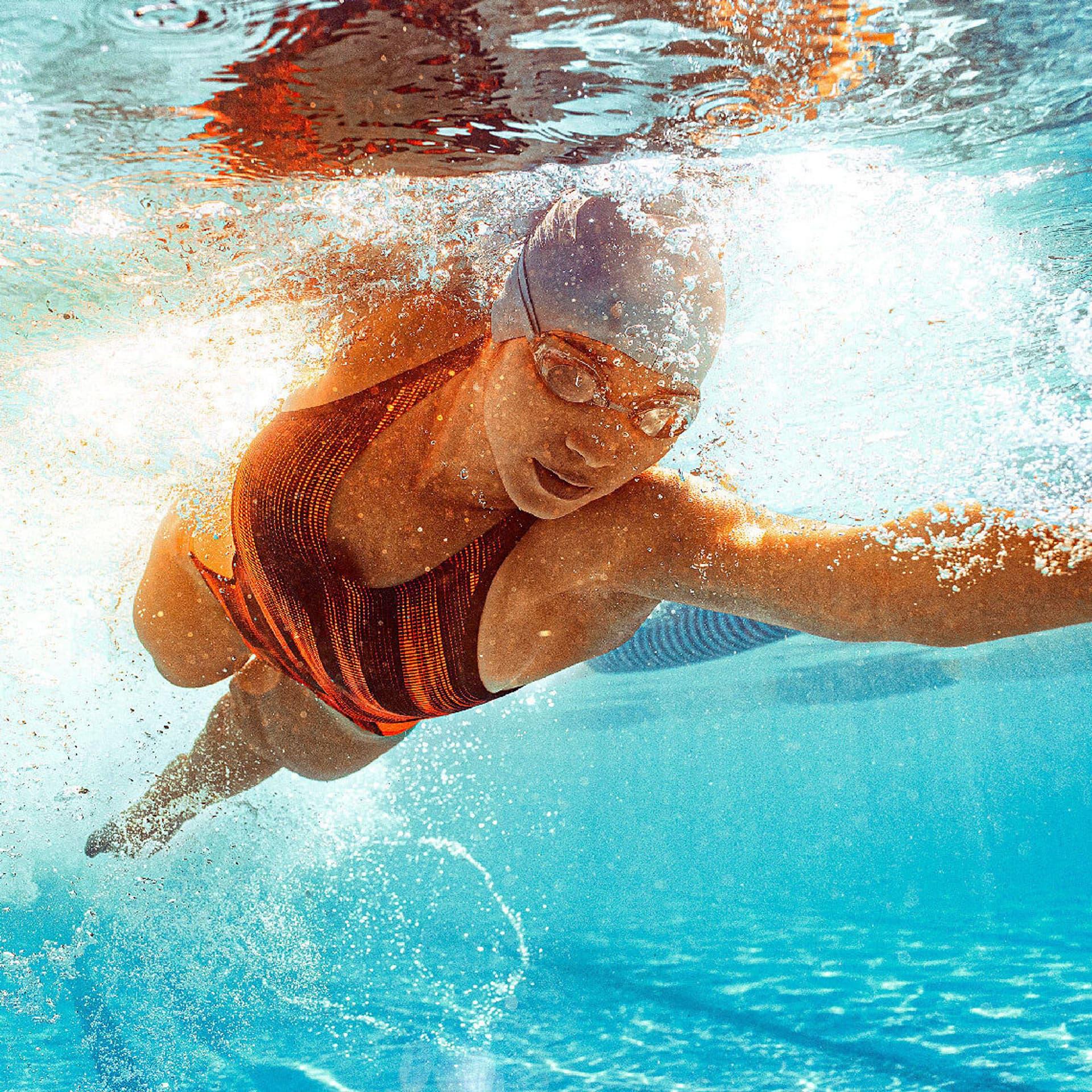 Eine Schwimmerin bei der Kraulbewegung. Ihr Kopf ist unter Wasser, ihren linken Arm streckt sie lang nach vorn.