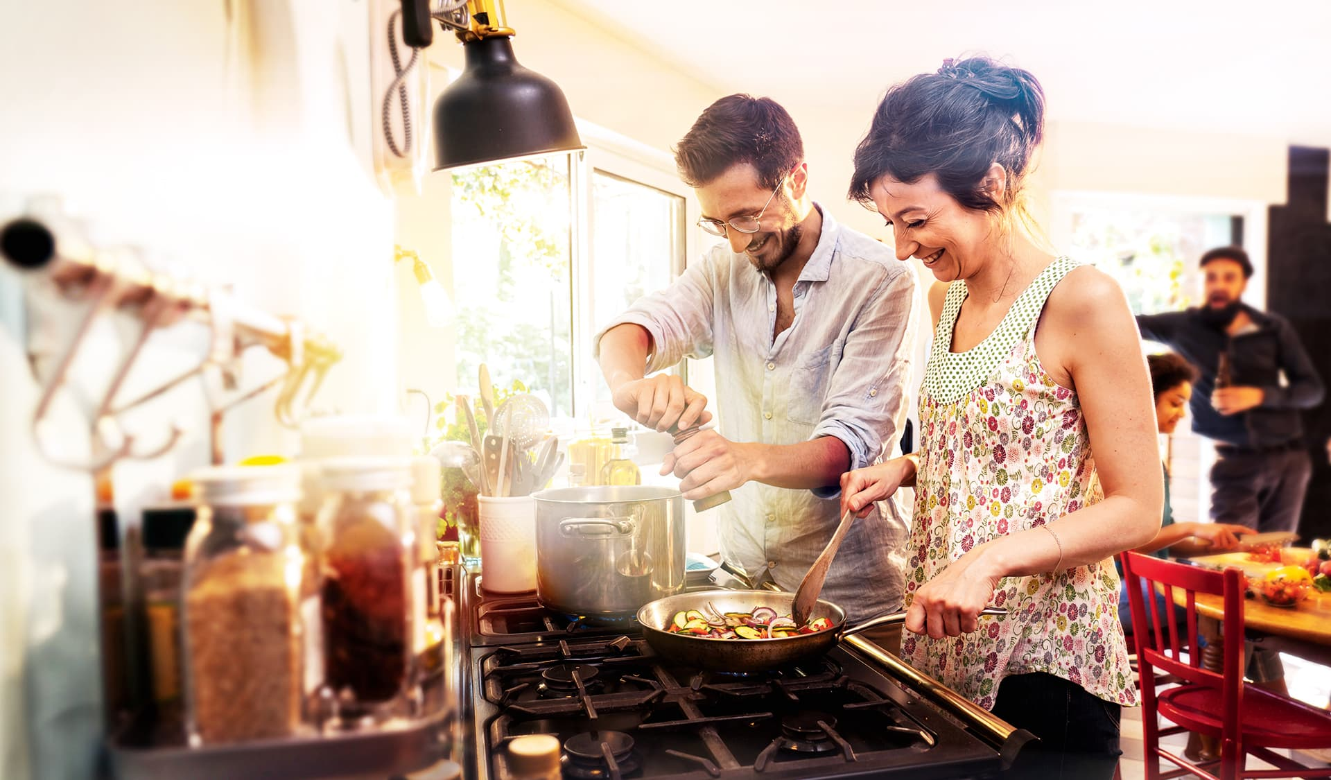 Mann und Frau in der Küche. Sie rührt in der Pfanne, er mahlt Pfeffer