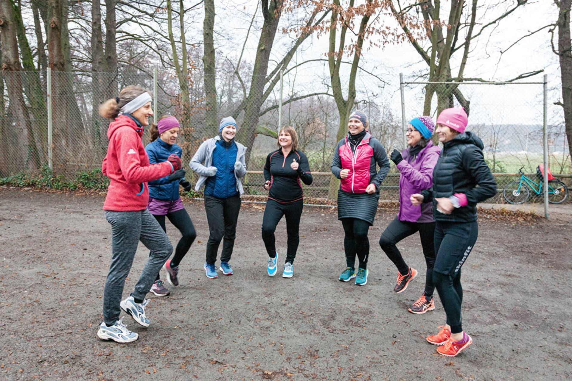 Sieben Teilnehmer beim Lauftraining wärmen sich auf