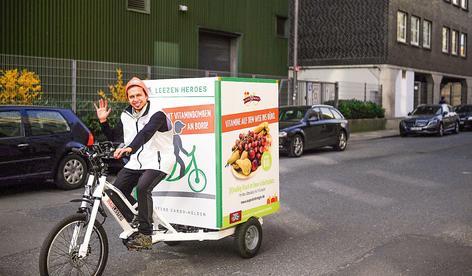 Mann auf Lastenfahrrad fährt Lebensmittel aus