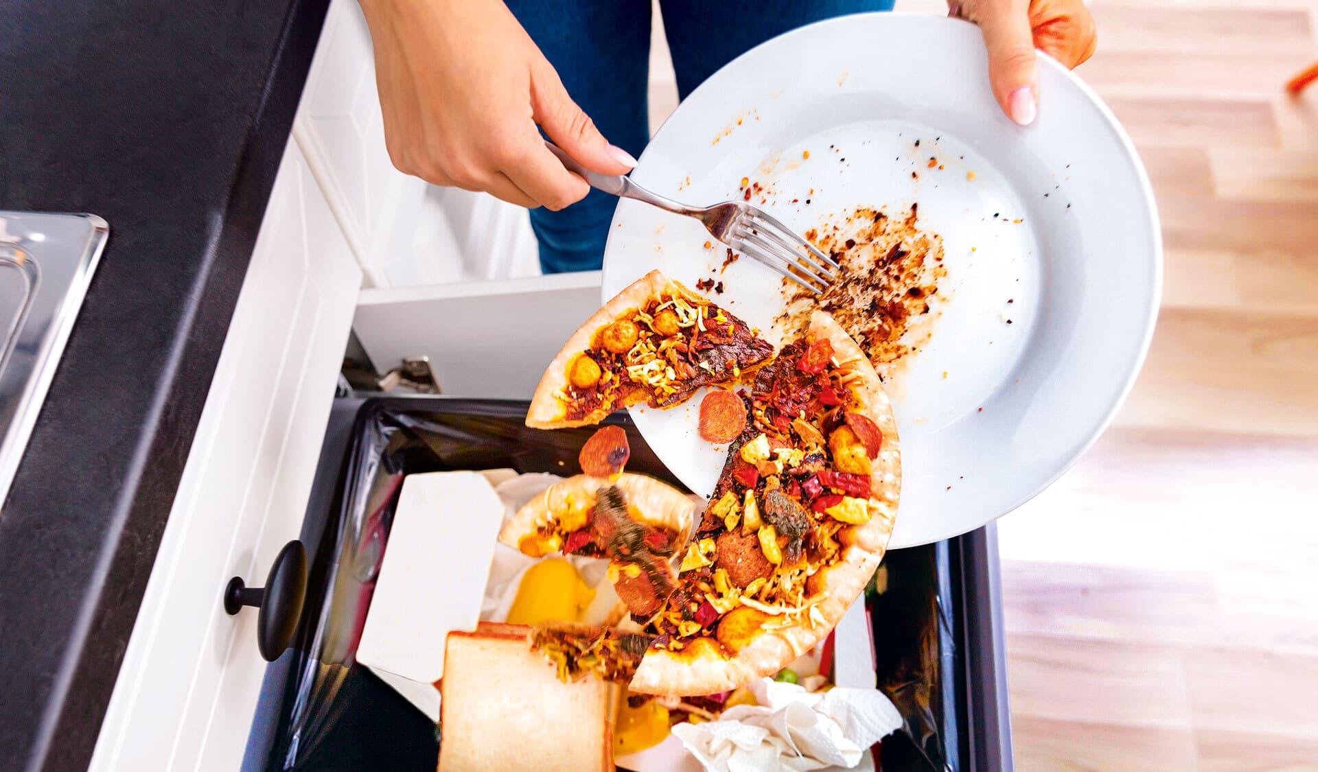 Eine halbe Pizza wird mit einer Gabel von einem Teller in einen Abfalleimer geworfen