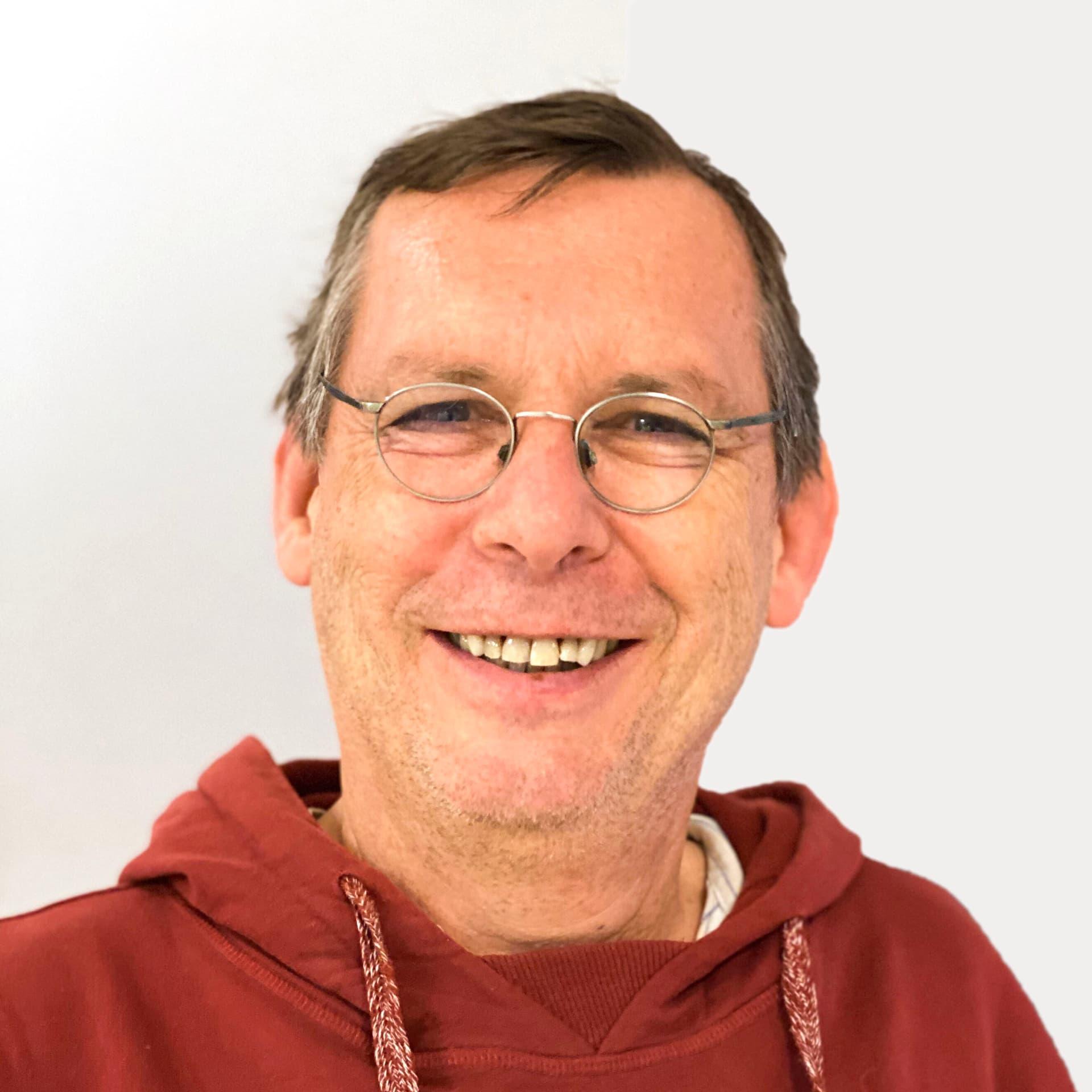 Ein Mann mit Brille vor grauem Hintergrund