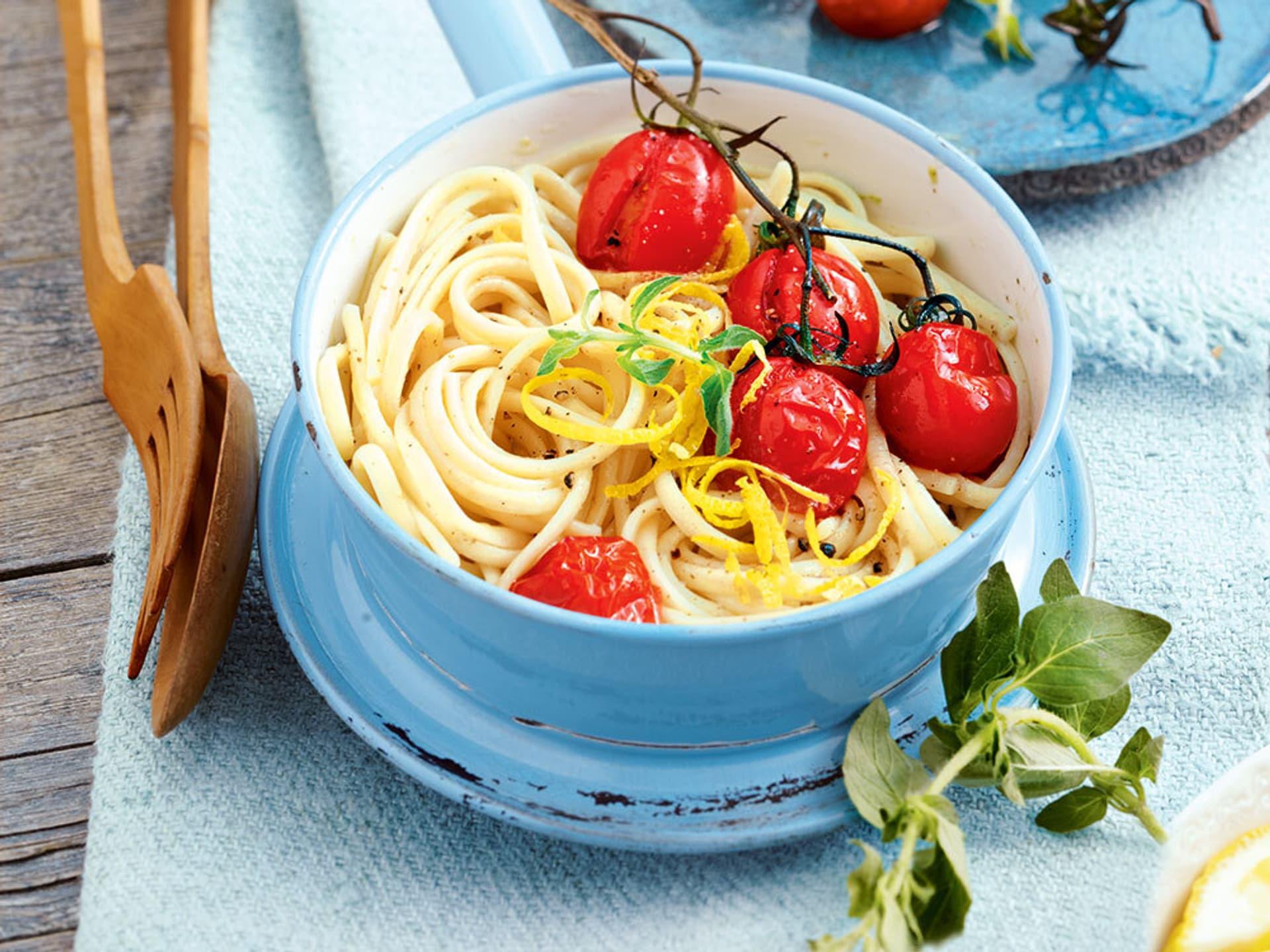 Nudeln mit geschmorten Tomaten in einer blauen Schale