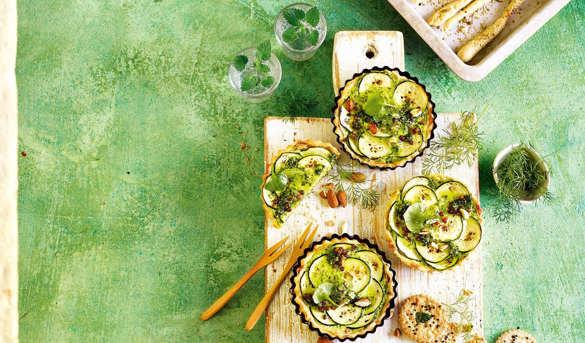 Törtchen mit Zucchini drappiert auf einem Brett