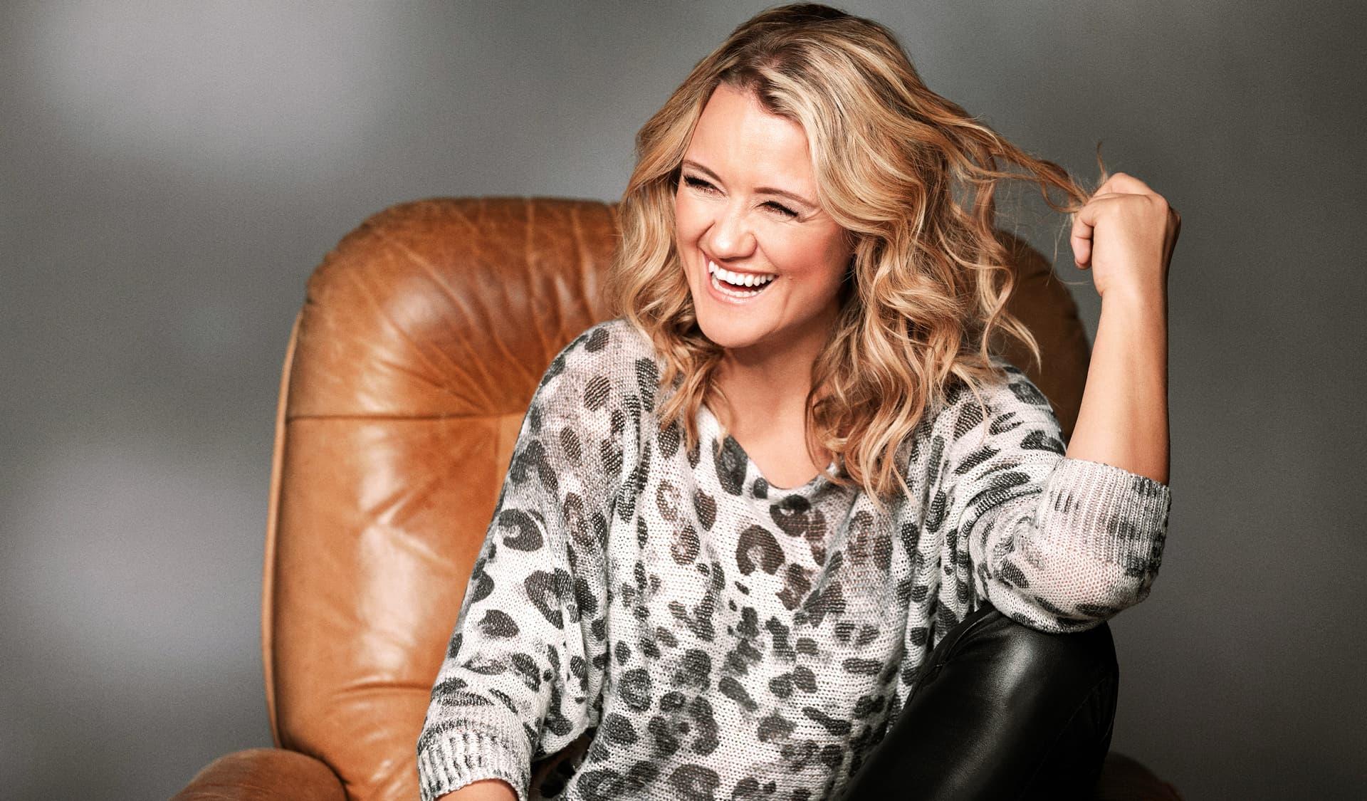 Lisa Feller sitzt lachend auf einem Ledersessel und dreht eine Haarlocke