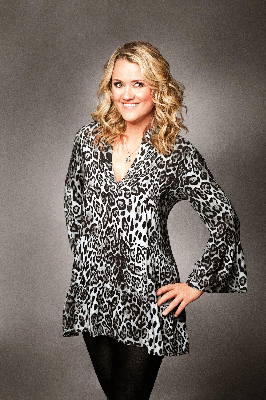 Lisa Feller in Leopardenprint-Bluse und schwarzer Hose vor grauen Hintergrund