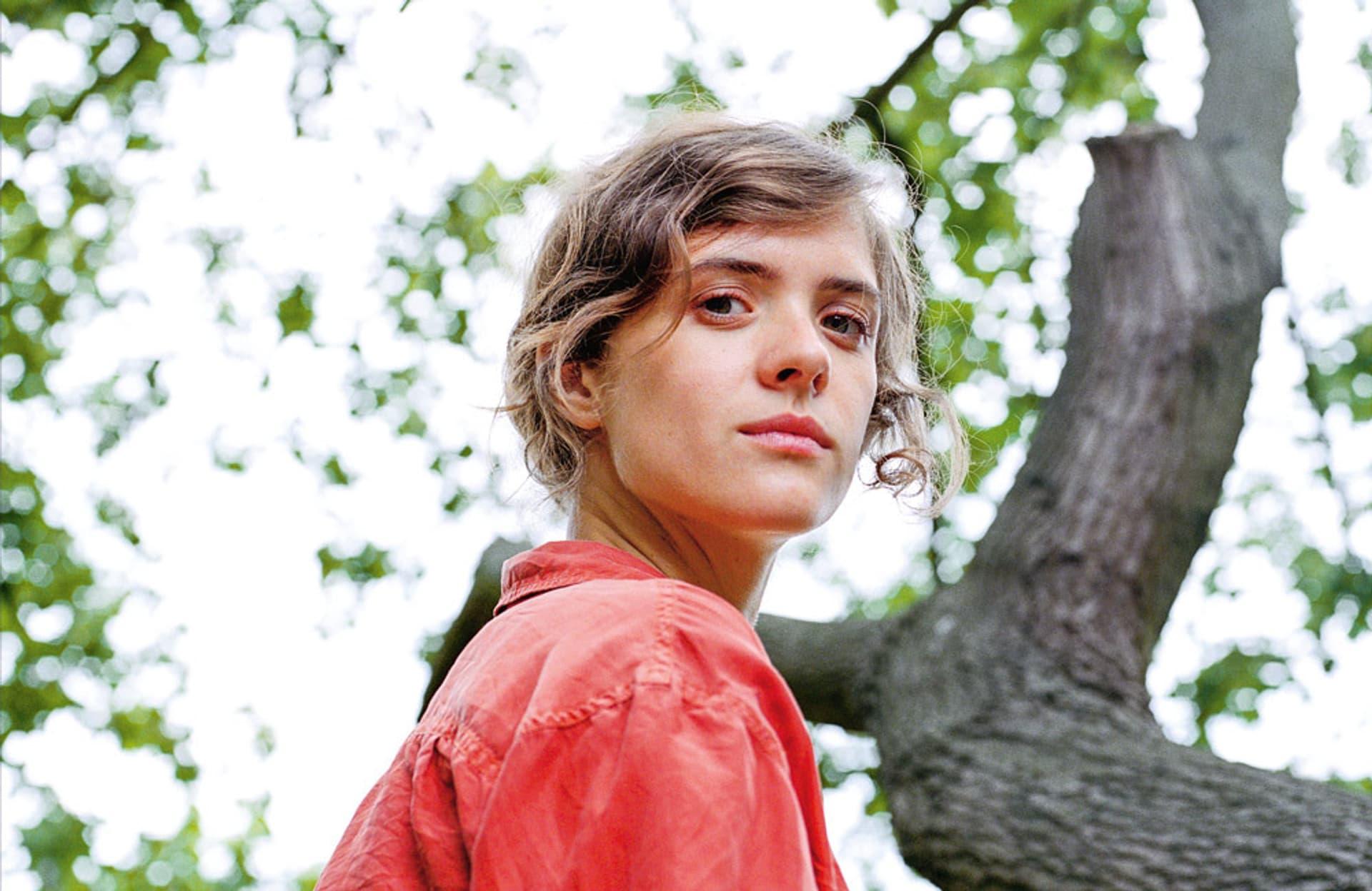 Schauspielerin Liv Lisa Fries in roter Bluse schaut aus dem Foto den Betrachter an - im Hintergrund: Baum und Himmel